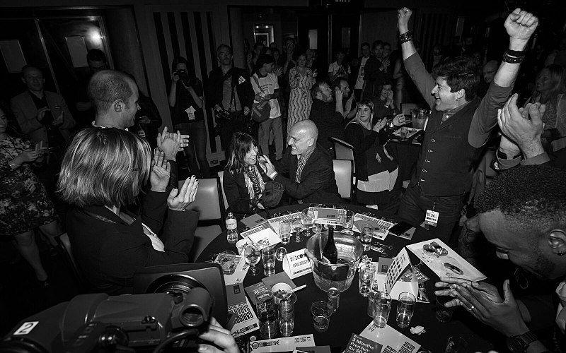 Une femme assise à une table ronde où se trouvent sept personnes réagit à l'annonce de sa victoire. Dans le fond, une foule de personnes se tiennent debout et l'applaudissent.
