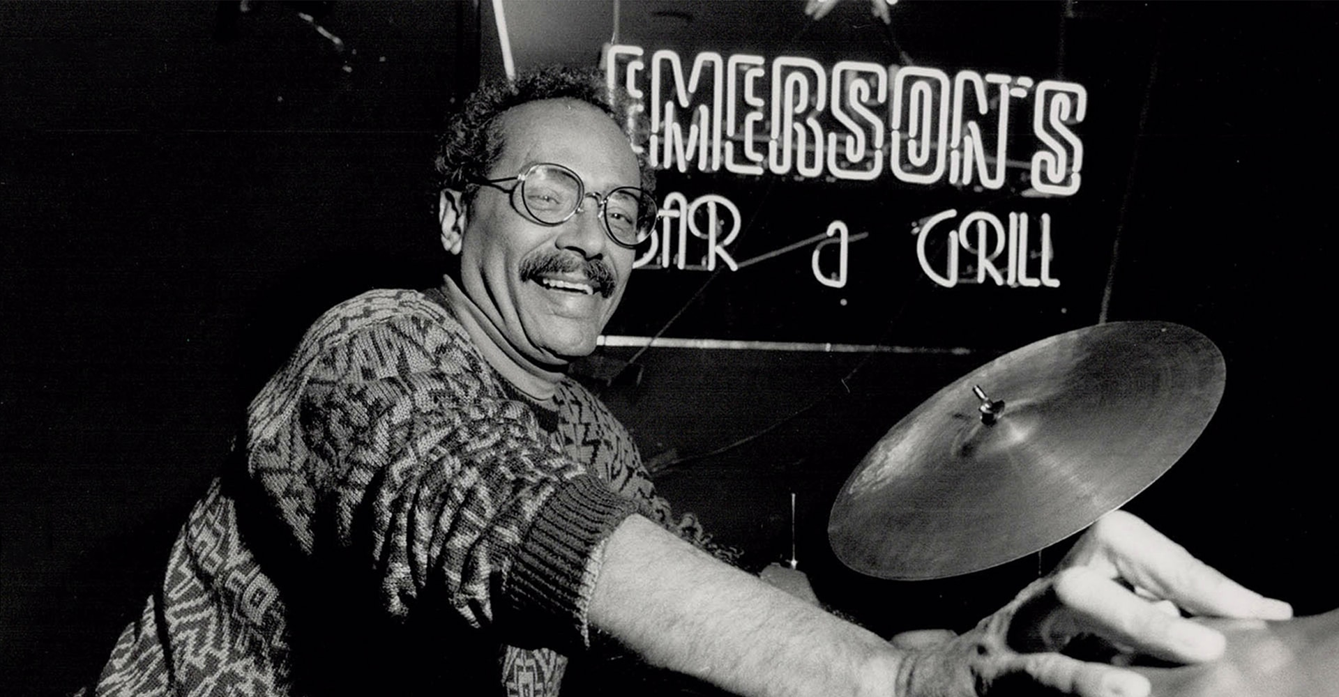 "A man with a moustache and glasses, with his sleeves rolls up, and his hand place on a cymbal of a drum kit. Behind him is a neon sign that reads ""Emerson's Bar & Grill""."