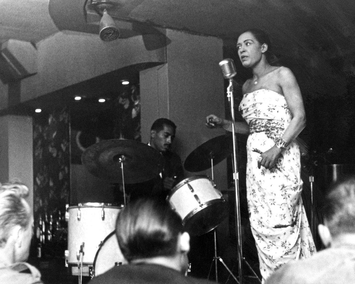 Une femme en robe bustier chante dans un micro sur scène. Un homme joue de la batterie derrière elle.