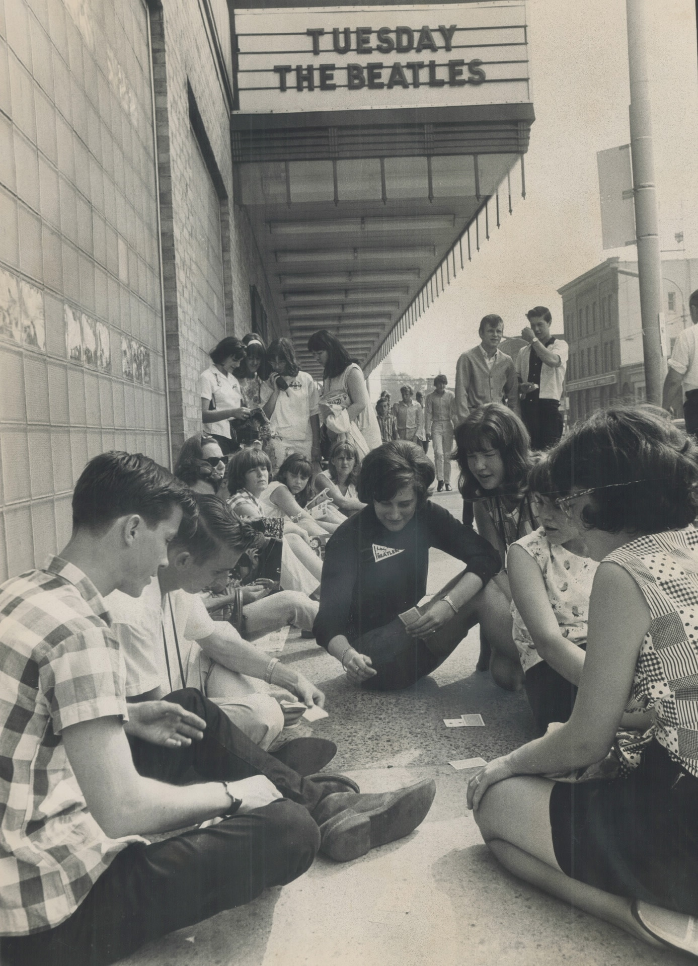 """A group of teenagers sitting on the street in front of an arena. The arena marquee sign reads: """"Tuesday: The Beatles"""""""
