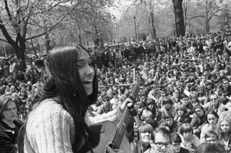 Woman with long hair playing an acoustic guitar sings in front of a crowd in an outdoor park.
