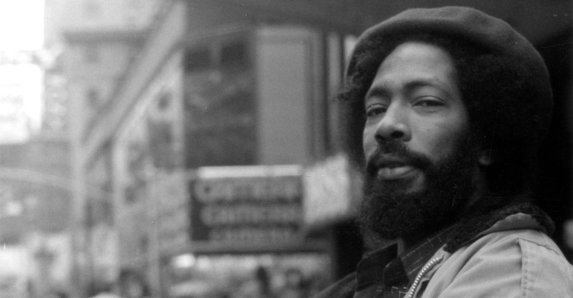 A man with a beard and afro, wearing a hat, looks at the camera. Behind him, out of focus, is a bustling urban street. Courtesy of Daniel Cauderion