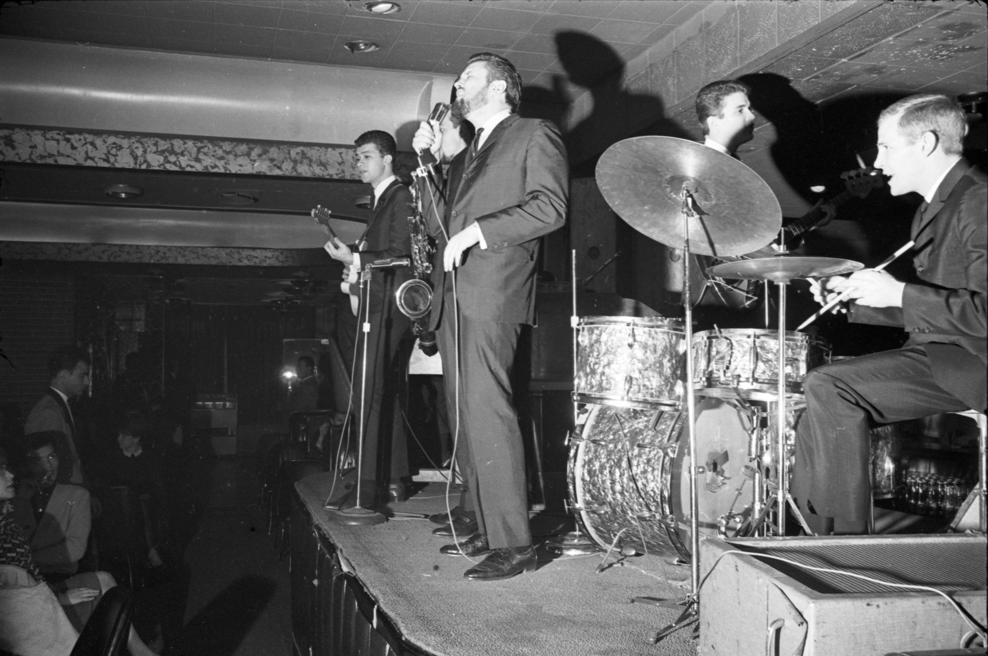 Five men on a stage with instruments wearing suits. Spectators can be seen in the lower left hand corner of the image.