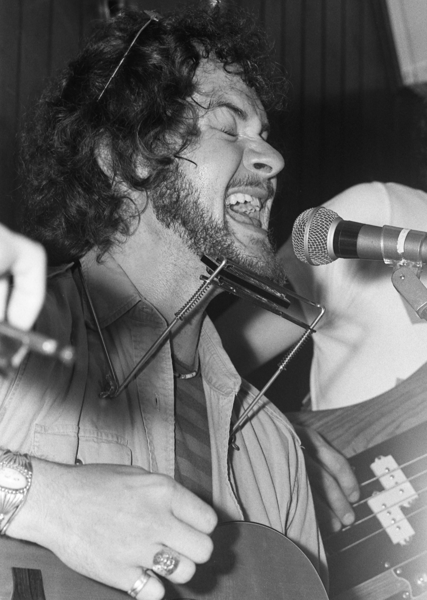 Man with curly hair and a scruffy beard sings into a microphone with his eyes closed and a harmonica around his neck.