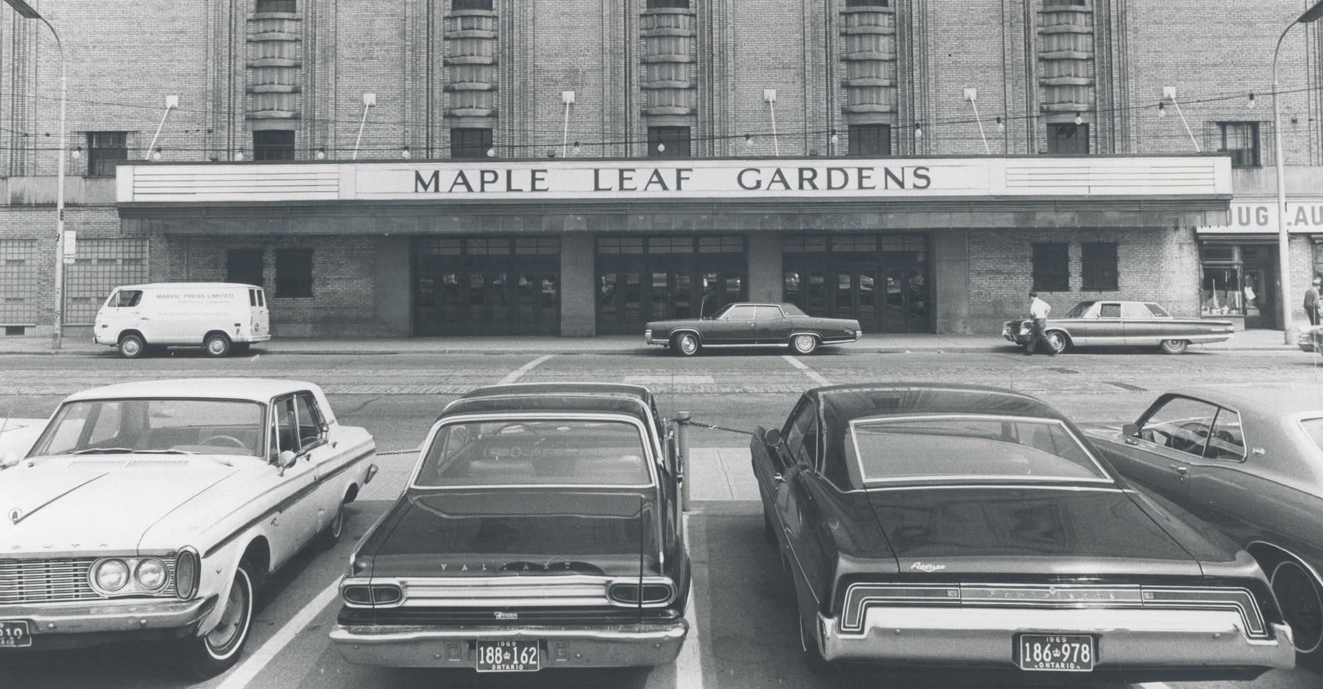 "Exterior of a building with a marquee that reads ""Maple Leaf Gardens"". In front, several cars are parked."