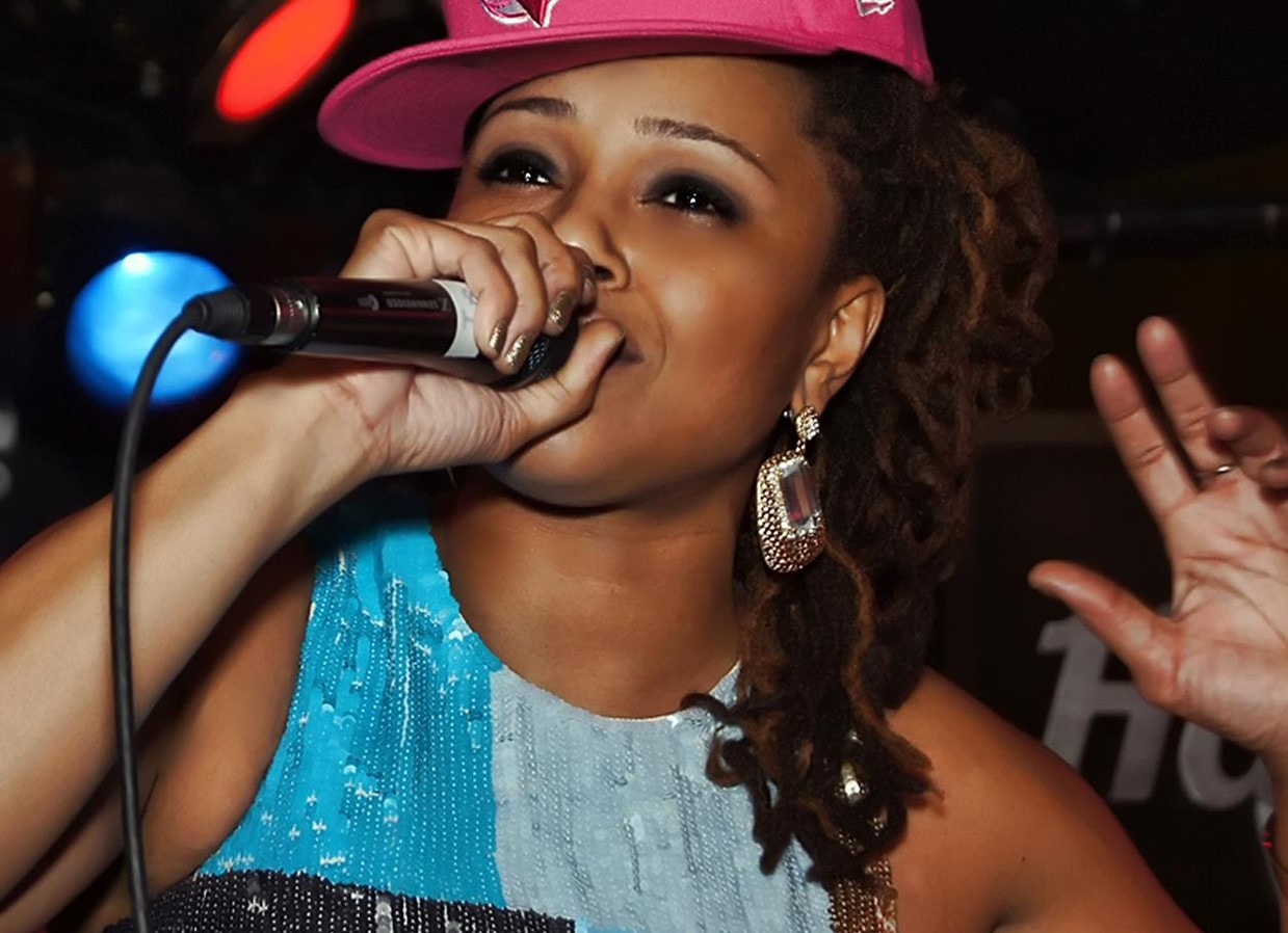 A woman in a pink baseball hat and blue shirt speaks into a microphone.