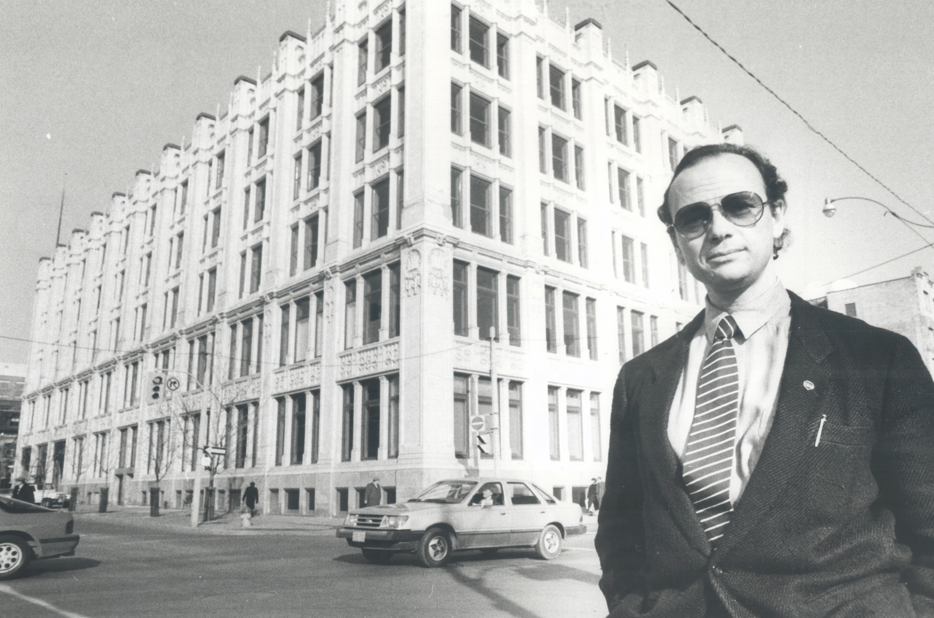A man wearing sunglasses and a suit stands on a street corner. Across the street, an ornate 5-storey building is visible.