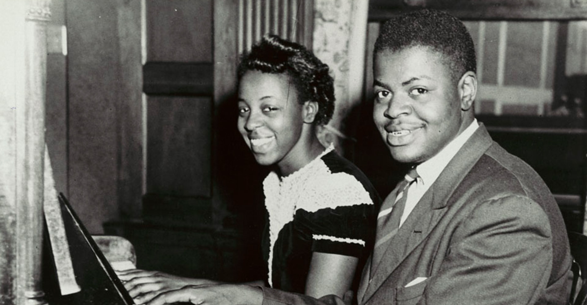 A young man and woman sit at a piano. They both face the camera and smile.