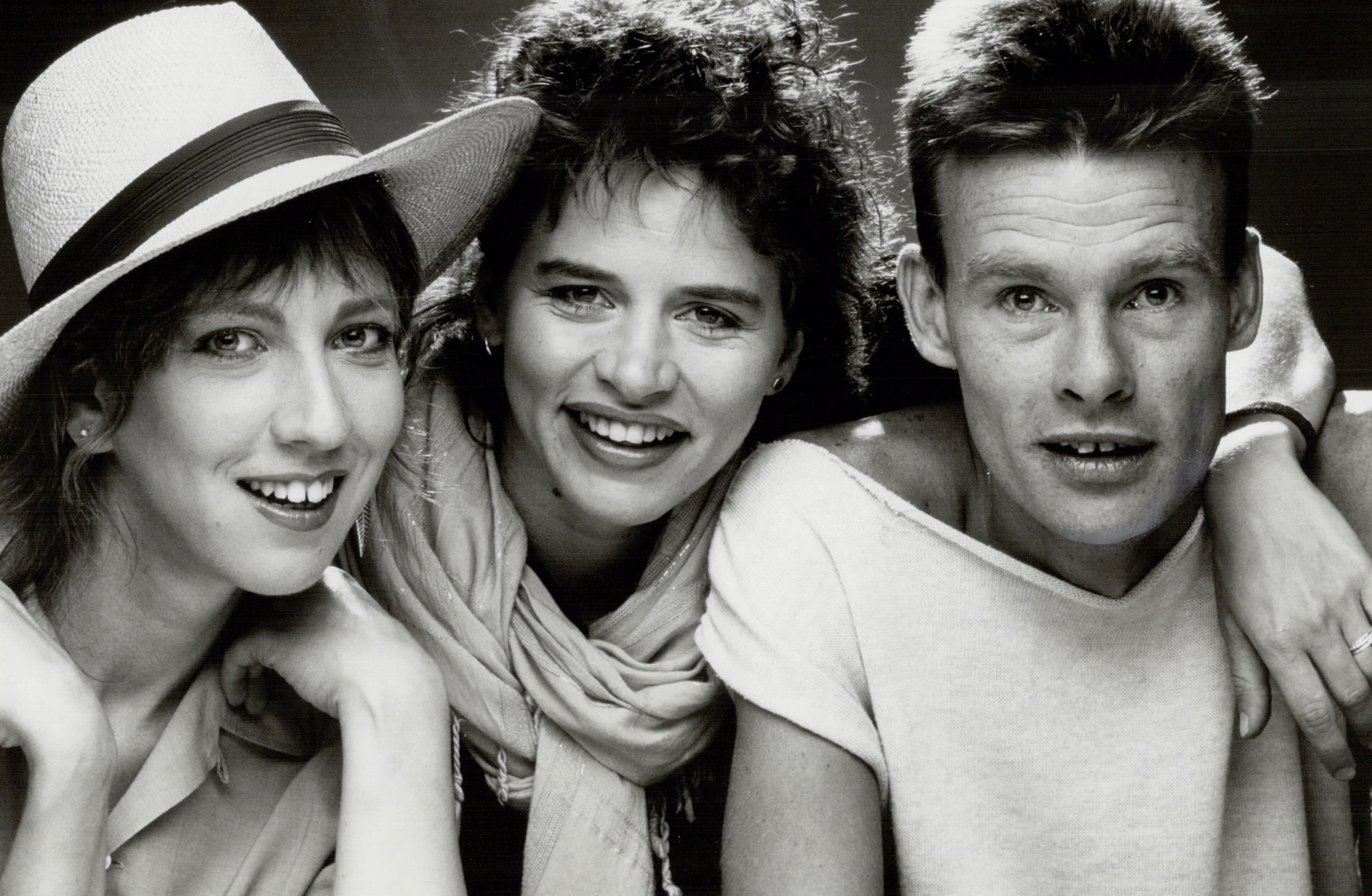 A portrait of three people, two women and one man. The woman on the far left is wearing a sun hat.
