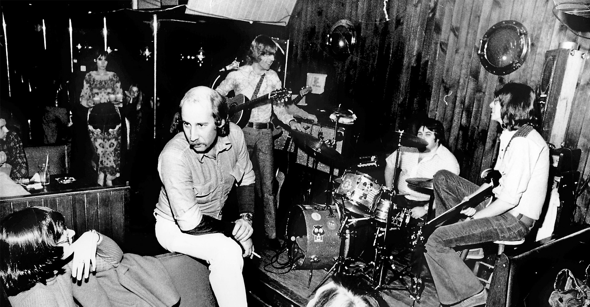 A black and white photograph of a group of people sitting around a stage inside a club. There is wood panelling on the walls and numerous musical instruments can be seen.