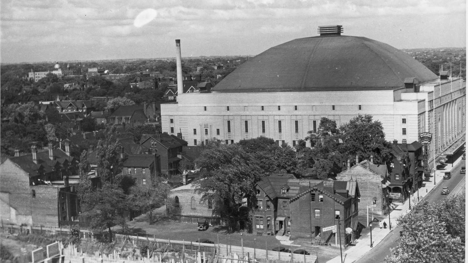 A black and white photograph of the exterior of Maple Leaf Gardens, a large arena, with trees surrounding the building and houses visible.