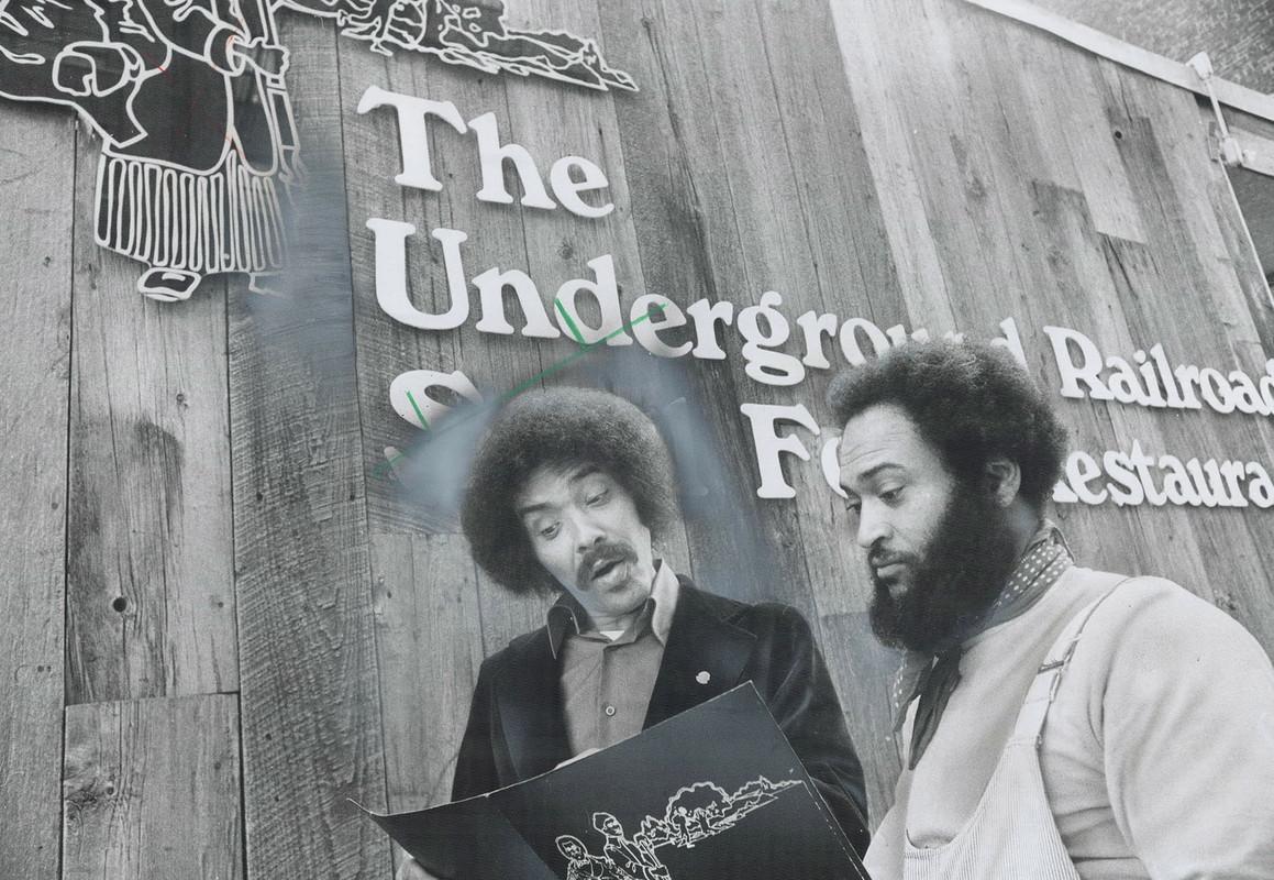 Deux hommes sont debout à l'extérieur d'un restaurant. Ils tiennent un morceau de papier et le regardent intensément. Les deux hommes ont les cheveux bouclés. L'un porte une moustache. L'autre a une barbe fournie.