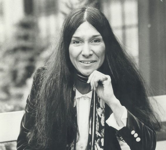 A woman with long dark hair sits with one leg crossed over the other, holding a flower in her left hand.