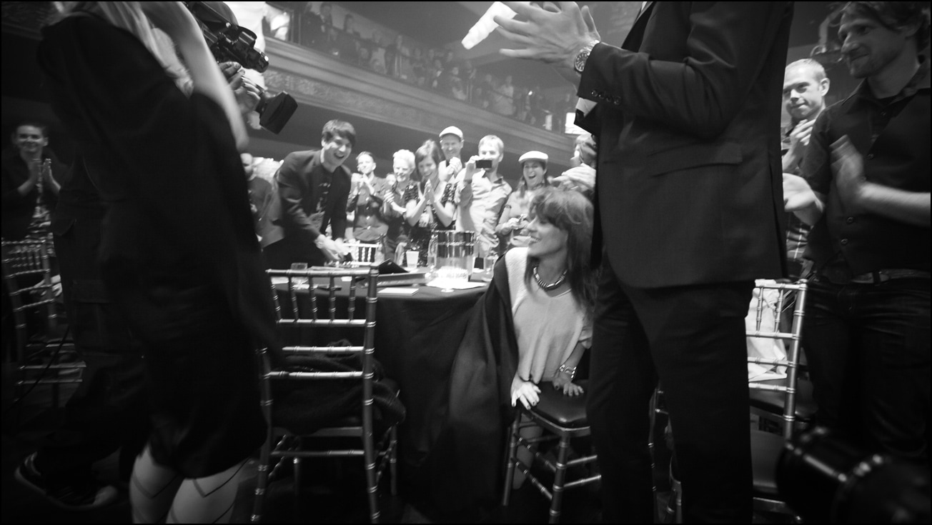 A woman peeks out from underneath a tablecloth as a crowd applauds.