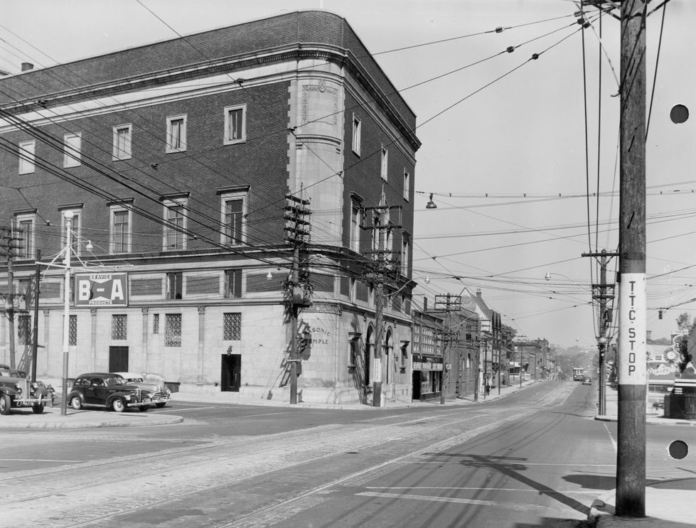 A black and white photograph of the exterior of a five-storey building on a curving street corner. The street is largely empty apart from one vintage car next to the building.