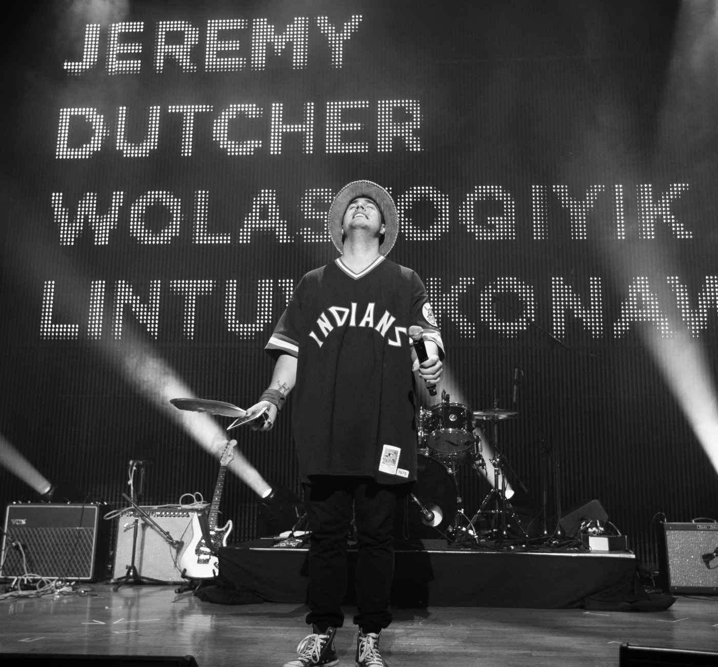 """Man stands on stage looking up smiling, he is wearing a sports jersey with 'Indians' on it, jeans and sneakers. Behind him a drum set, guitars and speakers are set up, further back a large screen reads """"JEREMY DUTCHER WOLASTOQIYIK LINTUWAKONAWA"""". On the far left, a female announcer smiles towards the audience."""