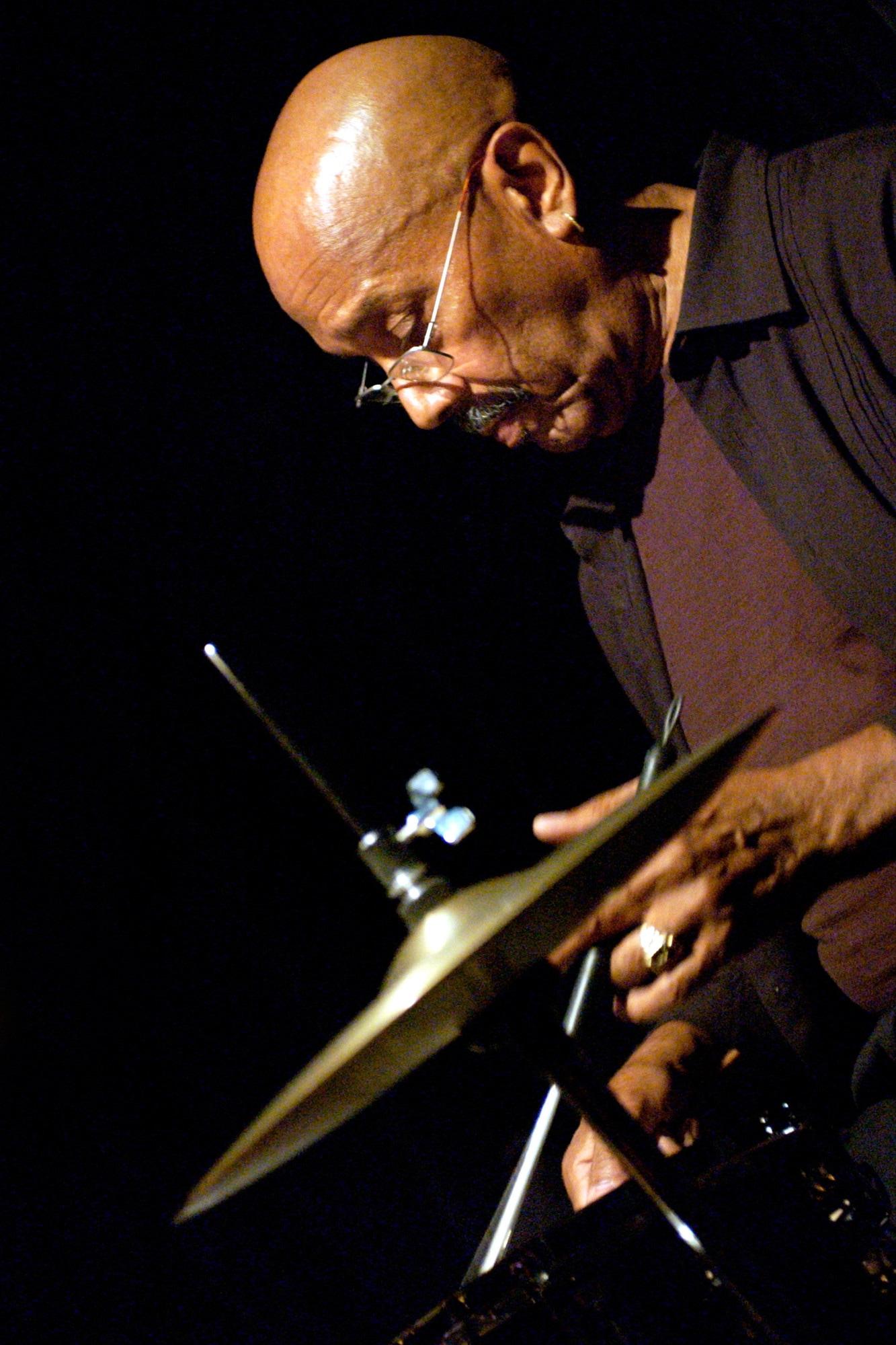 Un homme chauve à lunettes joue de la batterie.