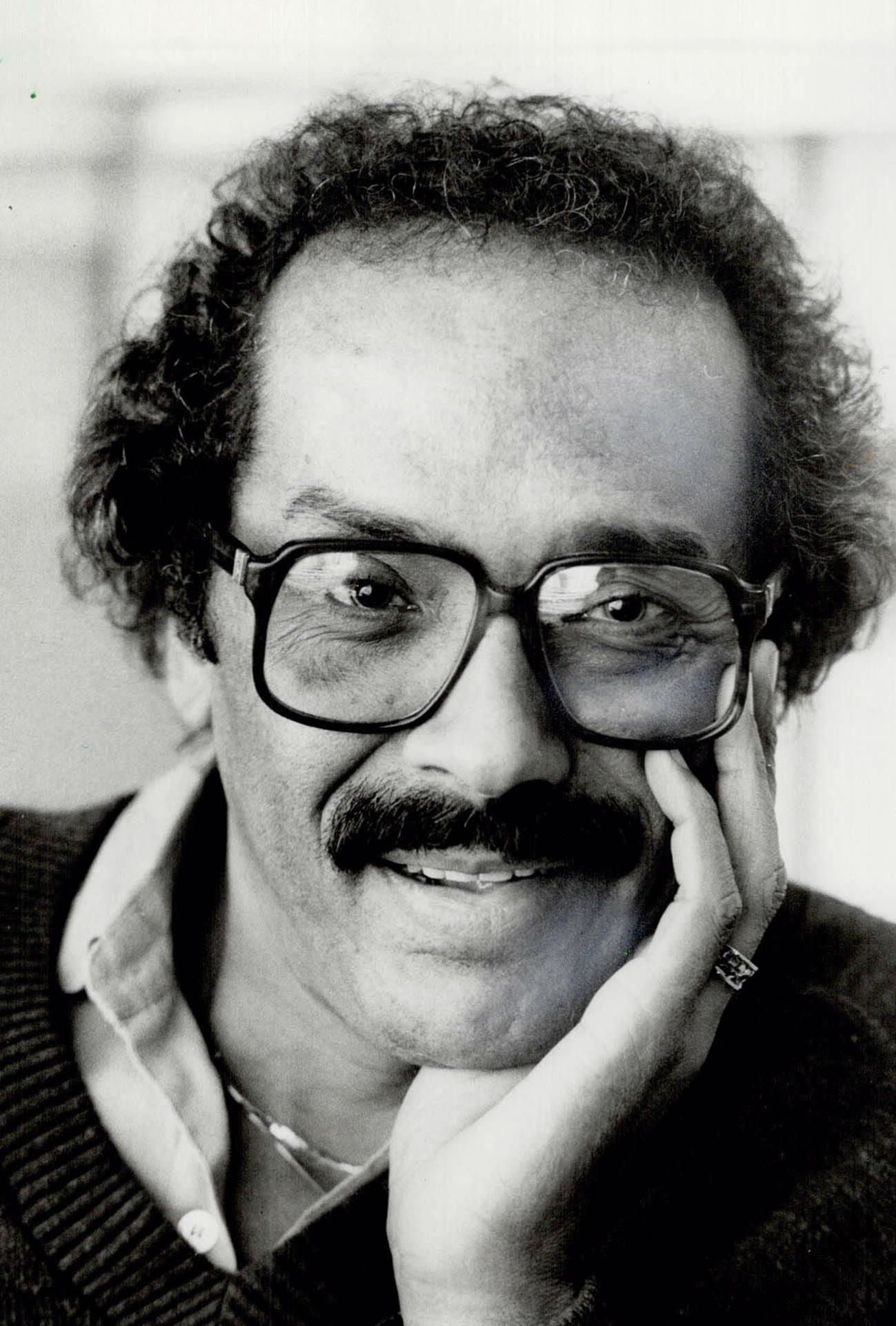 Un homme aux cheveux bouclés, portant des lunettes et une moustache, regarde la caméra.