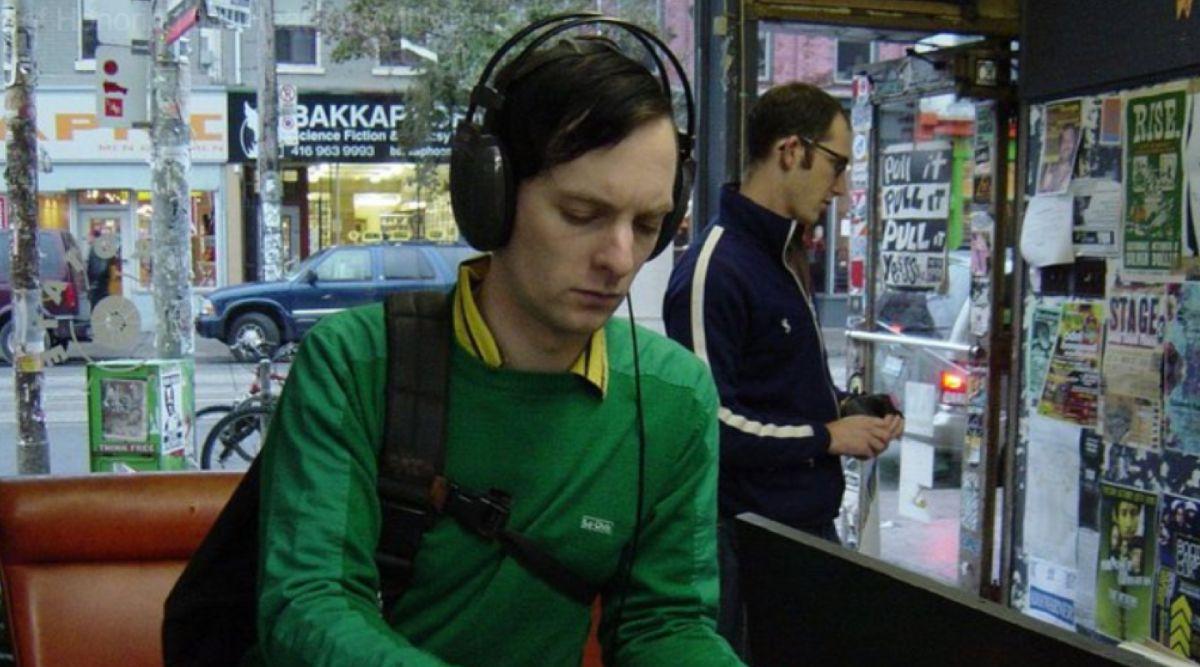 Photo de la tête et du haut du corps d'un jeune homme dans un magasin de disques et de livres. Il porte un chandail vert et de grands écouteurs sur les oreilles. Il porte aussi un sac à dos noir sur l'épaule droite.