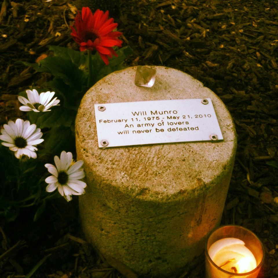 Une plaque commémorative circulaire entourée de marguerites gerberas rouges et blanches. Une pierre précieuse est placée au-dessus de la plaque.