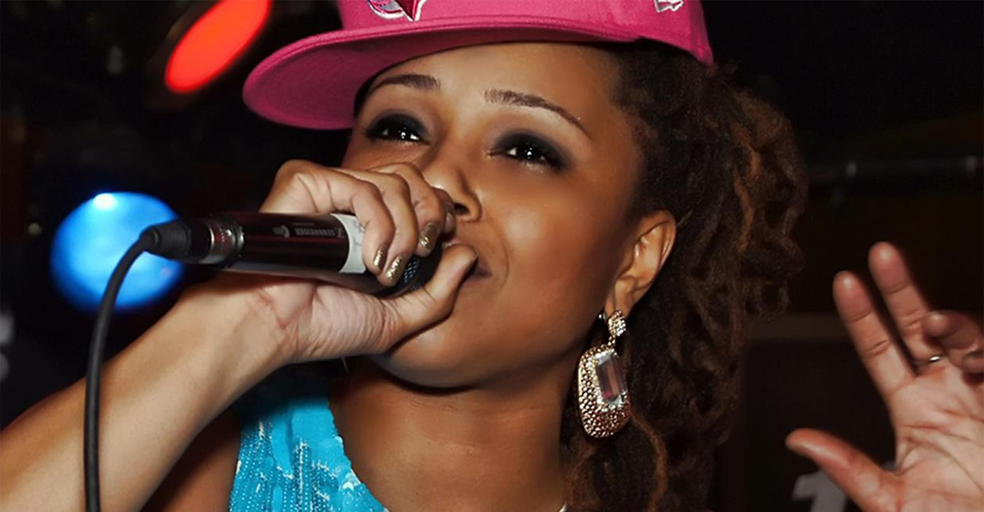 A woman wearing a Blue Jays baseball hat raps into a microphone
