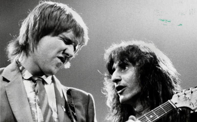 Close-up of two men, one holding a guitar and the other holding a bass. The guitar player has hit eye closed and is squinting. The bass player looks intensely at him.