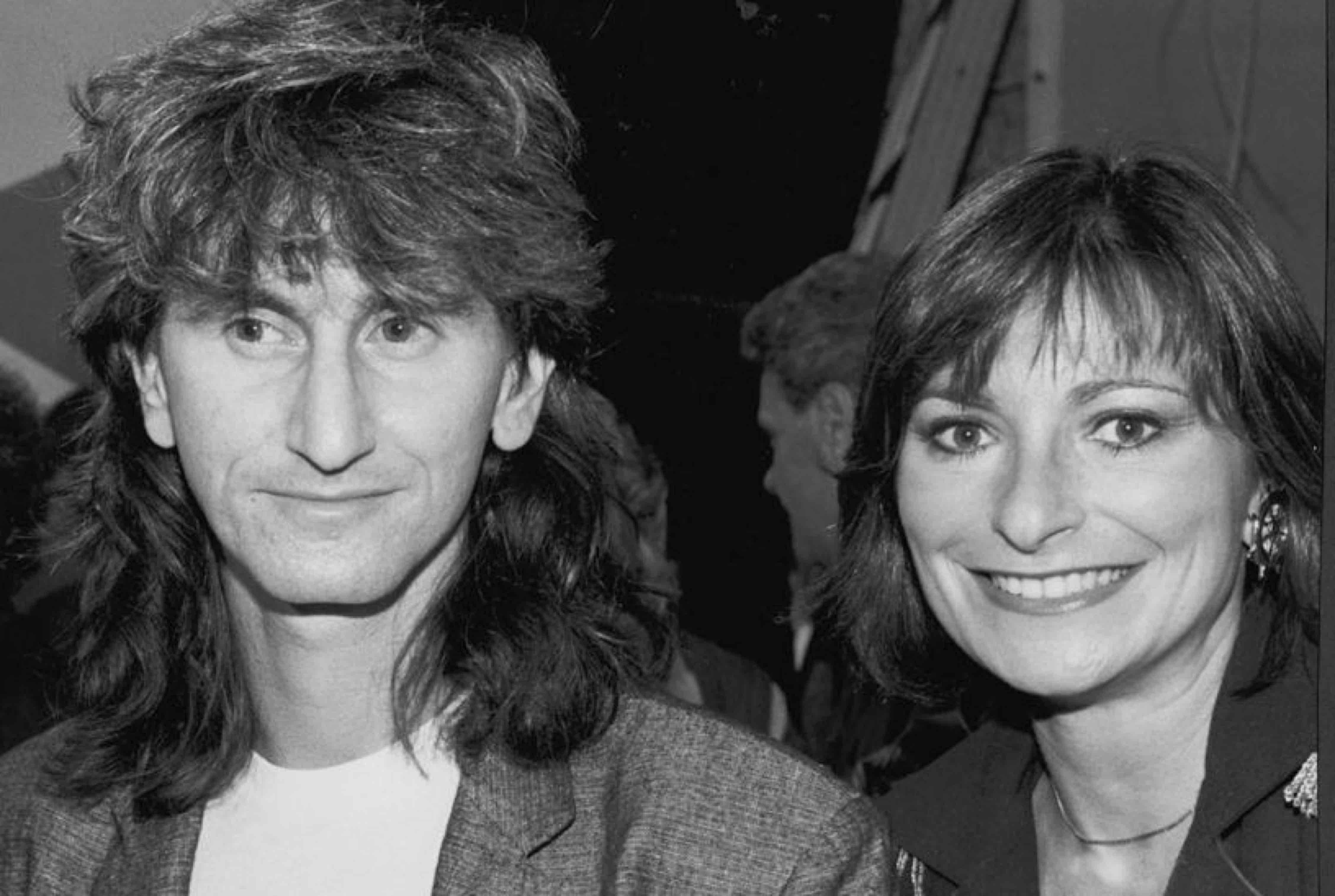Un homme aux cheveux aux épaules se tient à côté d'une femme aux cheveux courts.