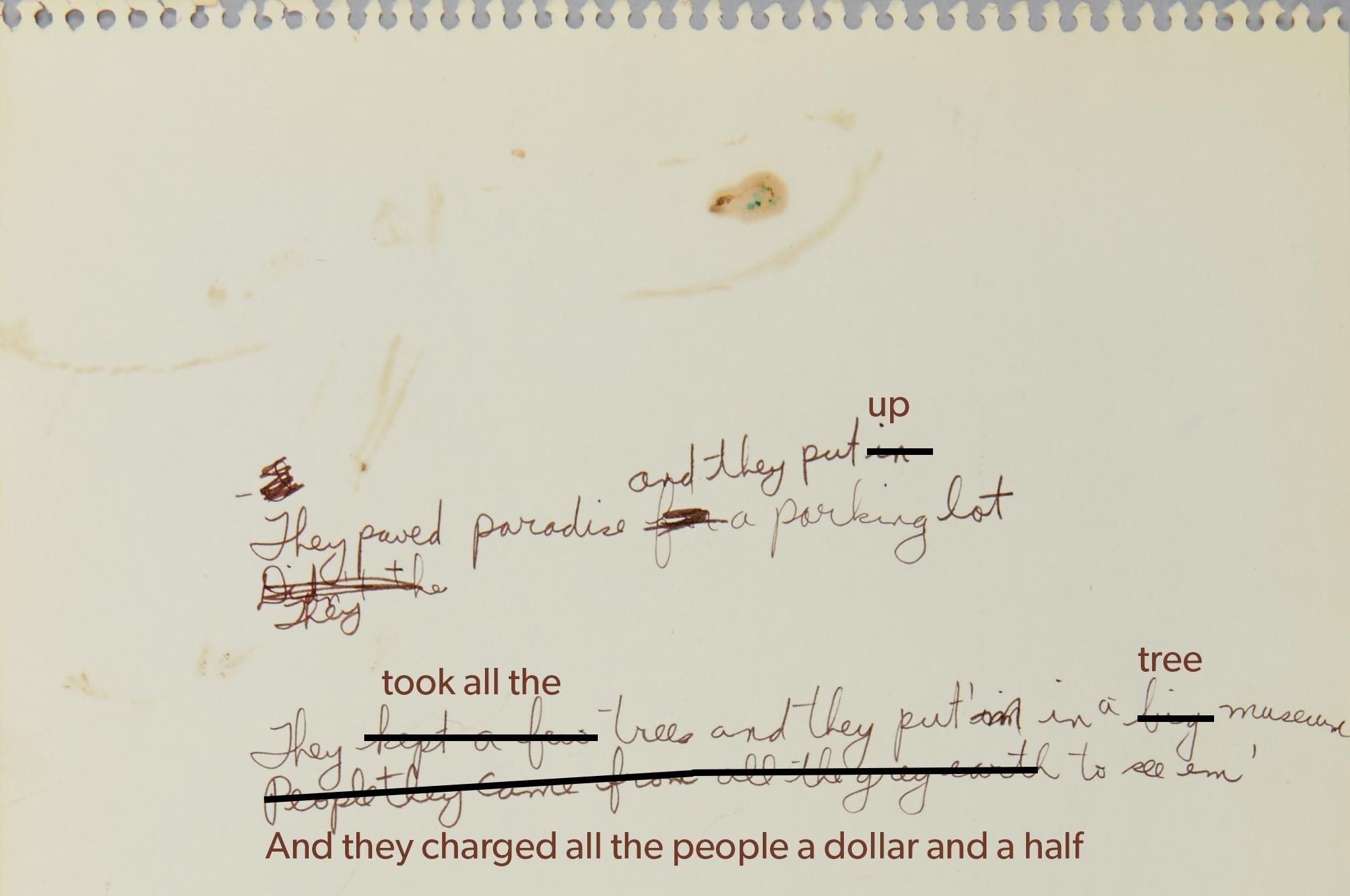 Morceau de papier jauni et légèrement taché déchiré d'un cahier à reliure à anneaux. On y voit des paroles écrites à l'encre brune. Sur la première ligne, il est écrit: «They paved paradise and they put in a parking lot». On peut voir que JoniMitchell avait d'abord écrit «They paved paradise for a parking lot», mais qu'elle a remplacé «for» par la version ci-dessus. Sur la ligne suivante, il est écrit: «They», et la ligne est incomplète. On peut voir qu'elle avait d'abord écrit «Didn't the», mais qu'elle a biffé ces paroles. Sur la dernière ligne, on lit «They kept a few trees and they put'm in a big museum / People they came from all the grey earth to see em» alors que «put'm» a remplacé «put'im».