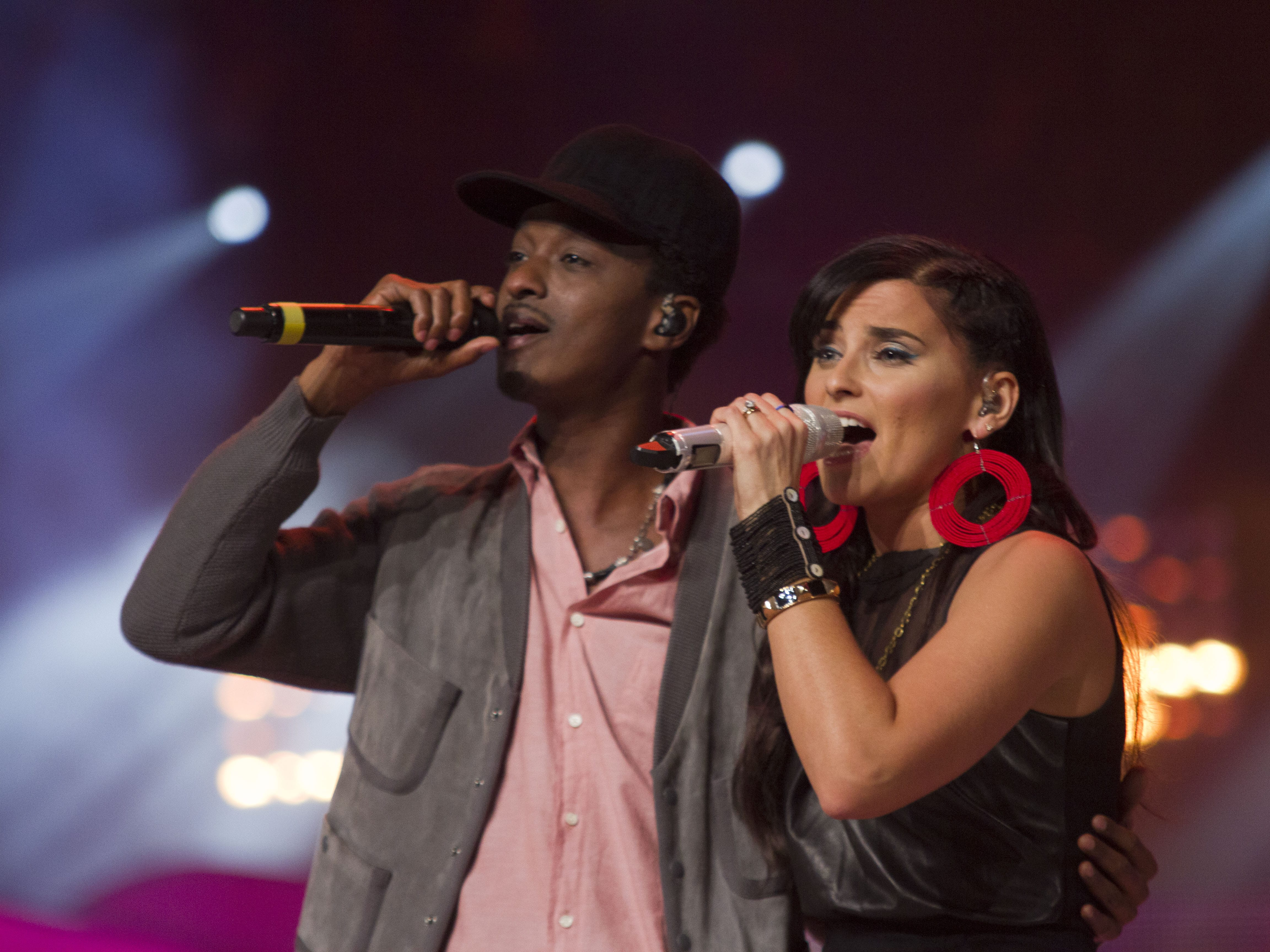 A man and woman sing into a microphone