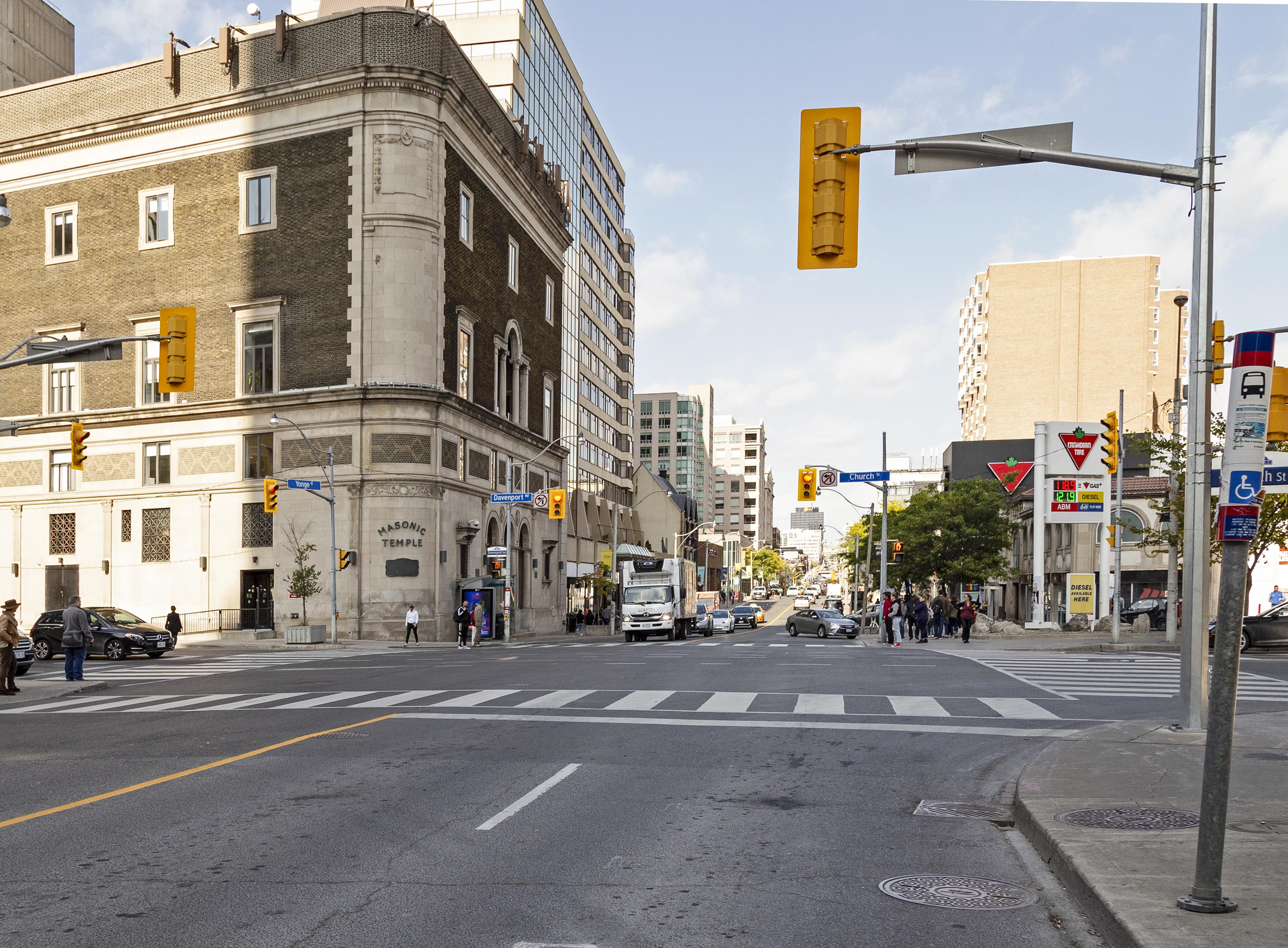 An intersection with a mid-rise building curving around the far corner. Hydro poles and a bus stop are on the right side of the image. Traffic lights are also found at the intersection.