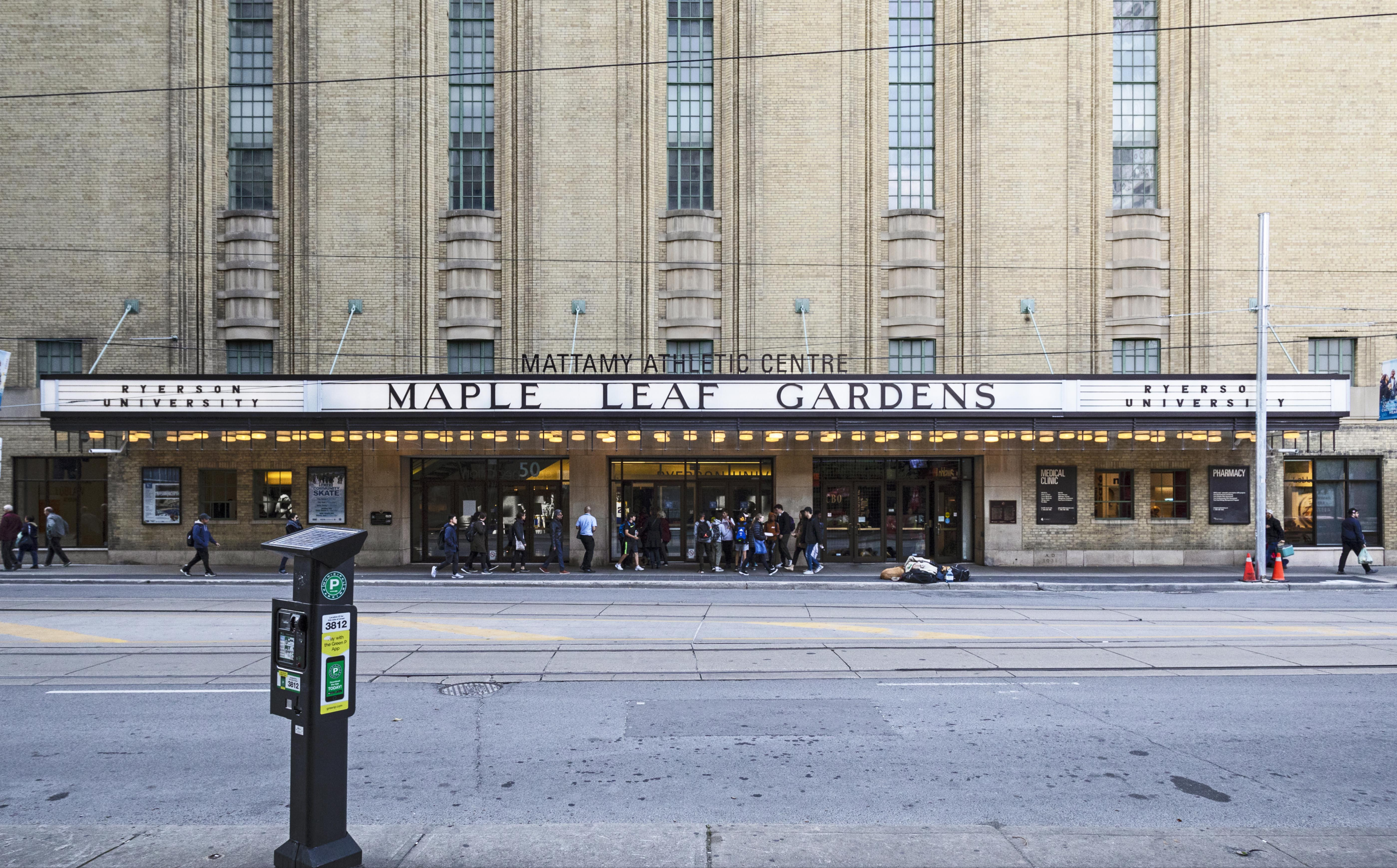 """Exterior of an imposing building with a maruqee that reads """"Maple Leaf Gardens"""". In the foreground there is a parking meter. Outside the building, people stand around."""