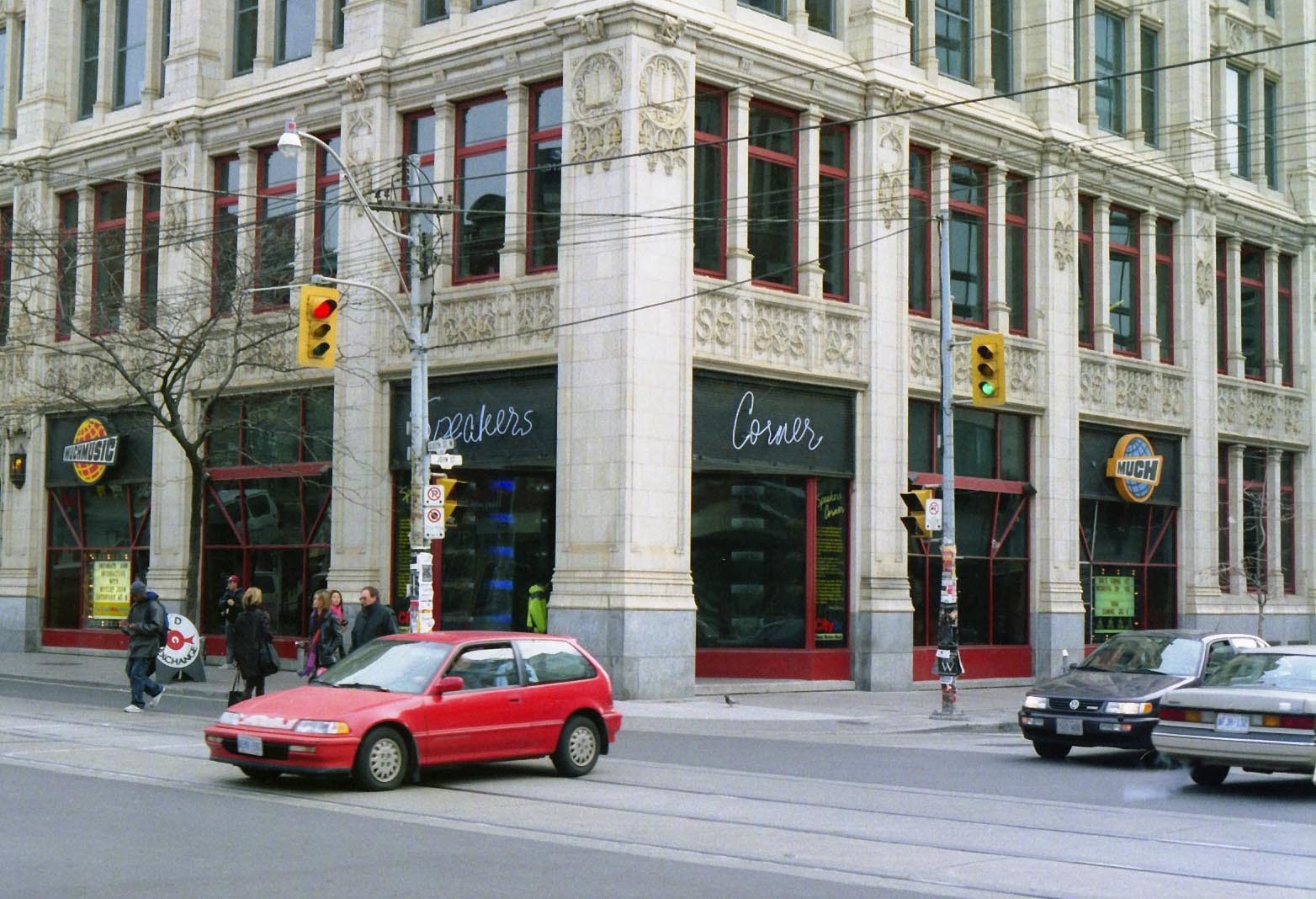 "Streetcorner with a gothic style building on an overcast cold day. A red hatchback car drives through the intersection as six pedestrians cross at the light wearing jackets and tuques. White neon letters reading ""Speakers Corner"" flank the corner of the building, along with the MuchMusic logo and Much sign."