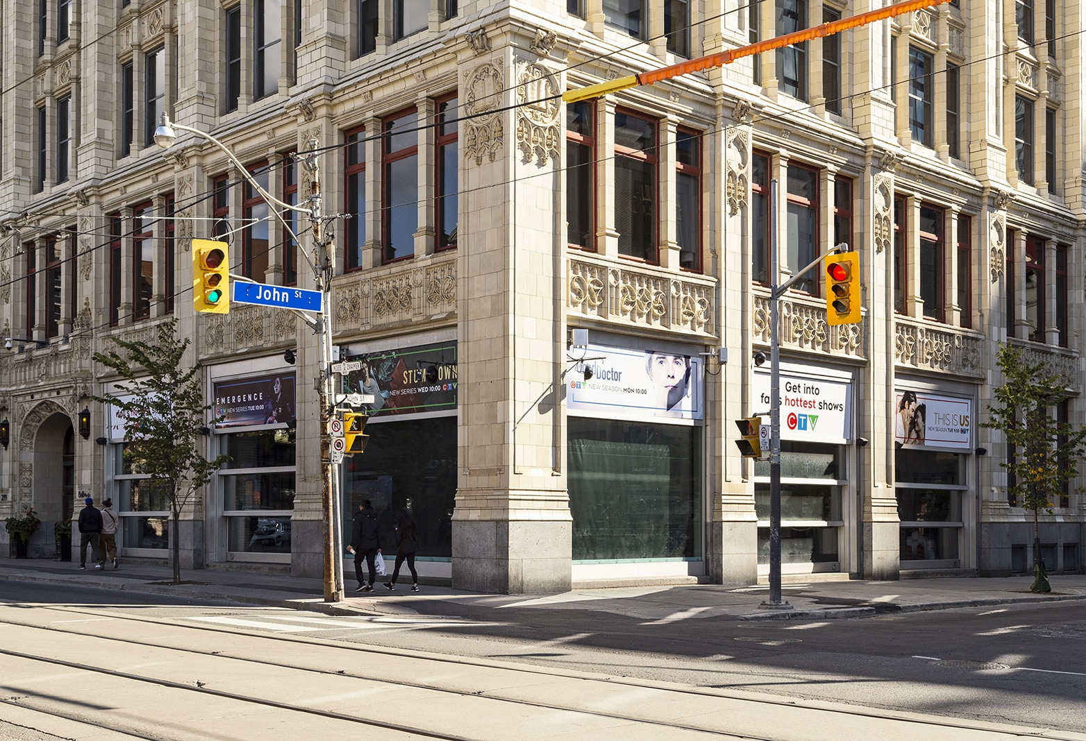 "Brightly lit street corner of gothic style building on a sunny Fall day. Television promotional advertisements are seen in the corner windows. Streetcar tracks run in foreground, as two sets of two people walk parallel along the sidewalk. Streetlights and a blue street sign saying ""John St"" are visisble on the left hand side."