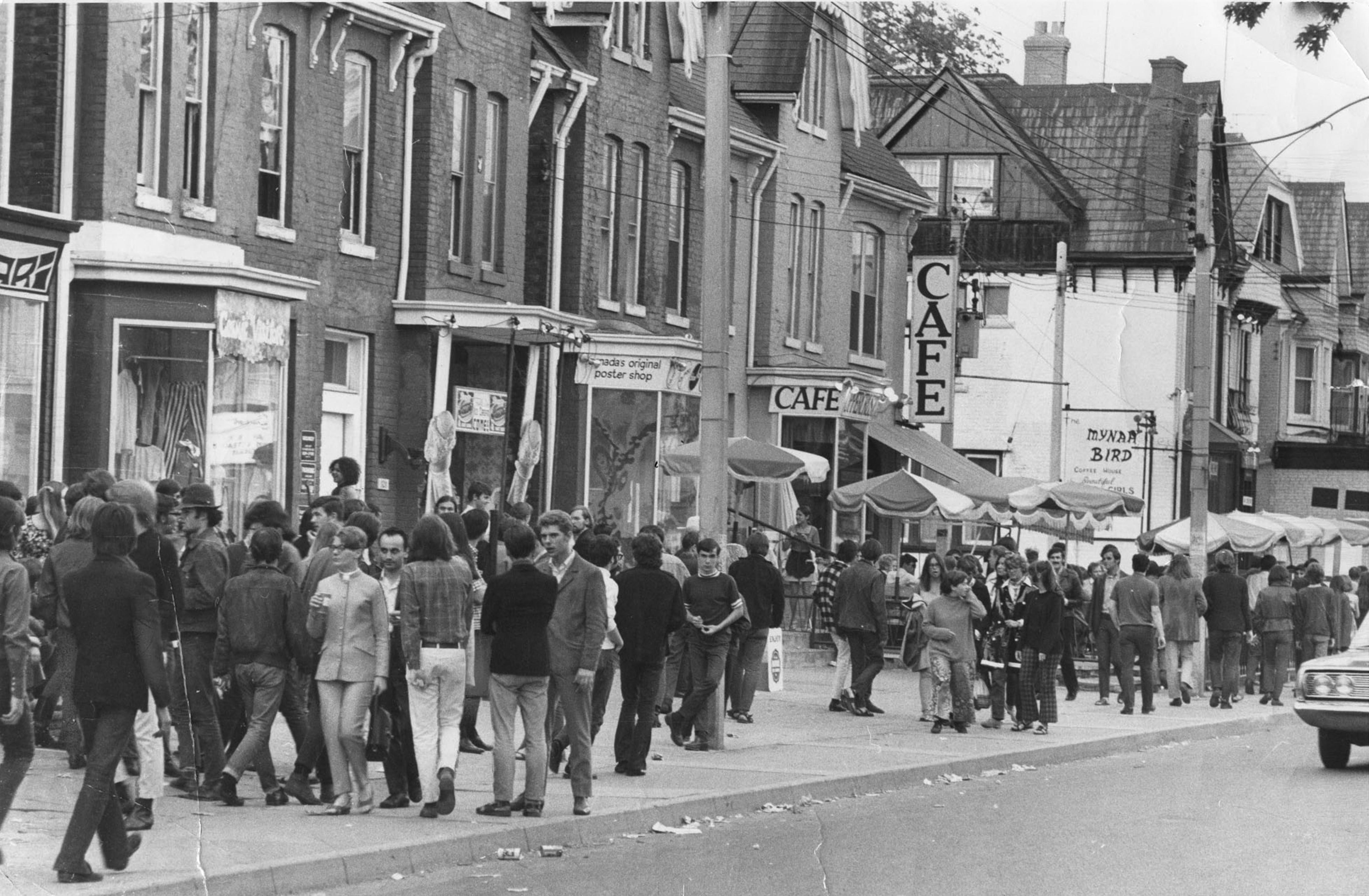 A black and white photograph of a street with large groups of people crowding the sidewalks along Yorkville avenue.