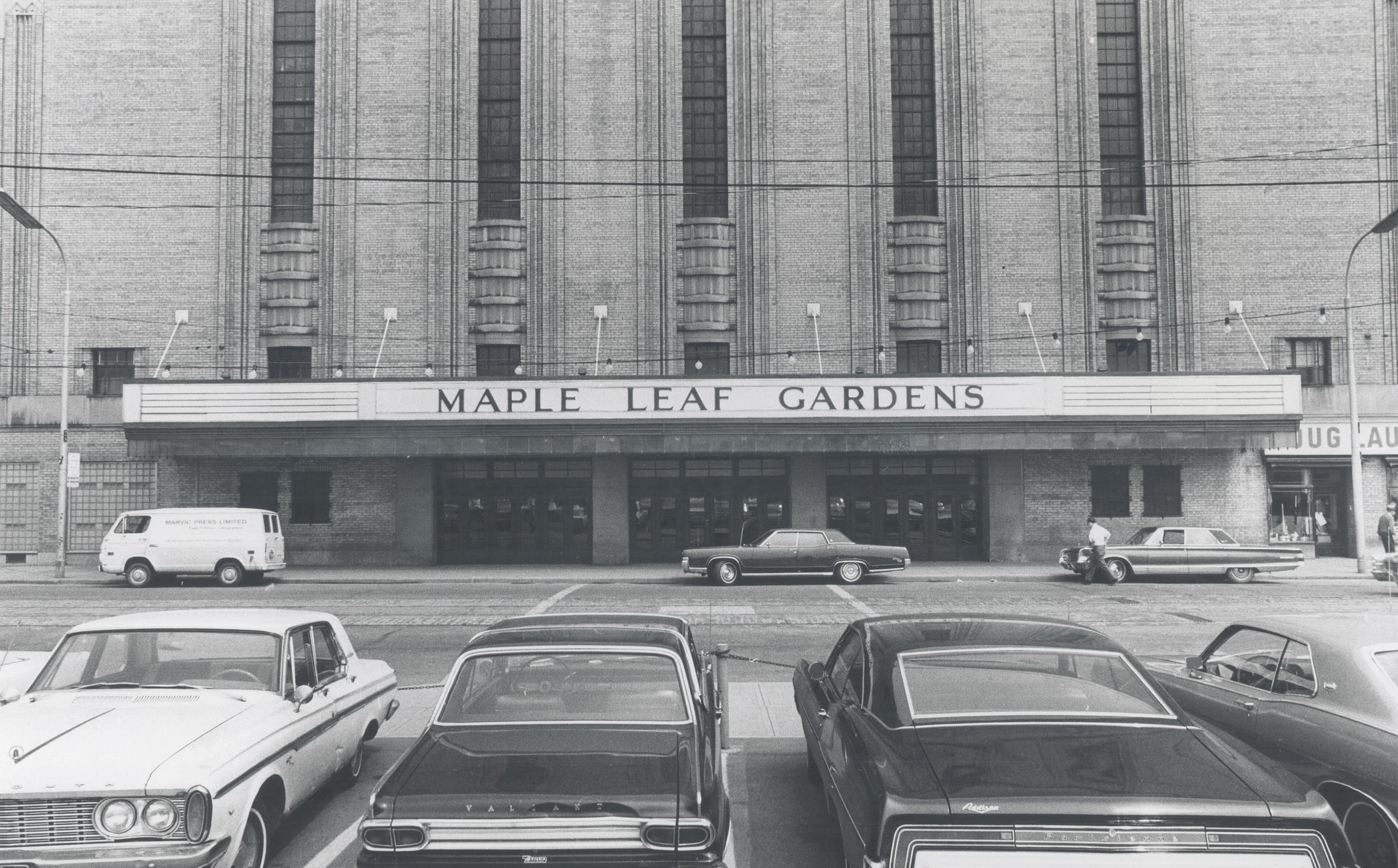 """Exterior of an imposing building with a maruqee that reads """"Maple Leaf Gardens"""". In the foreground are four parked cars."""