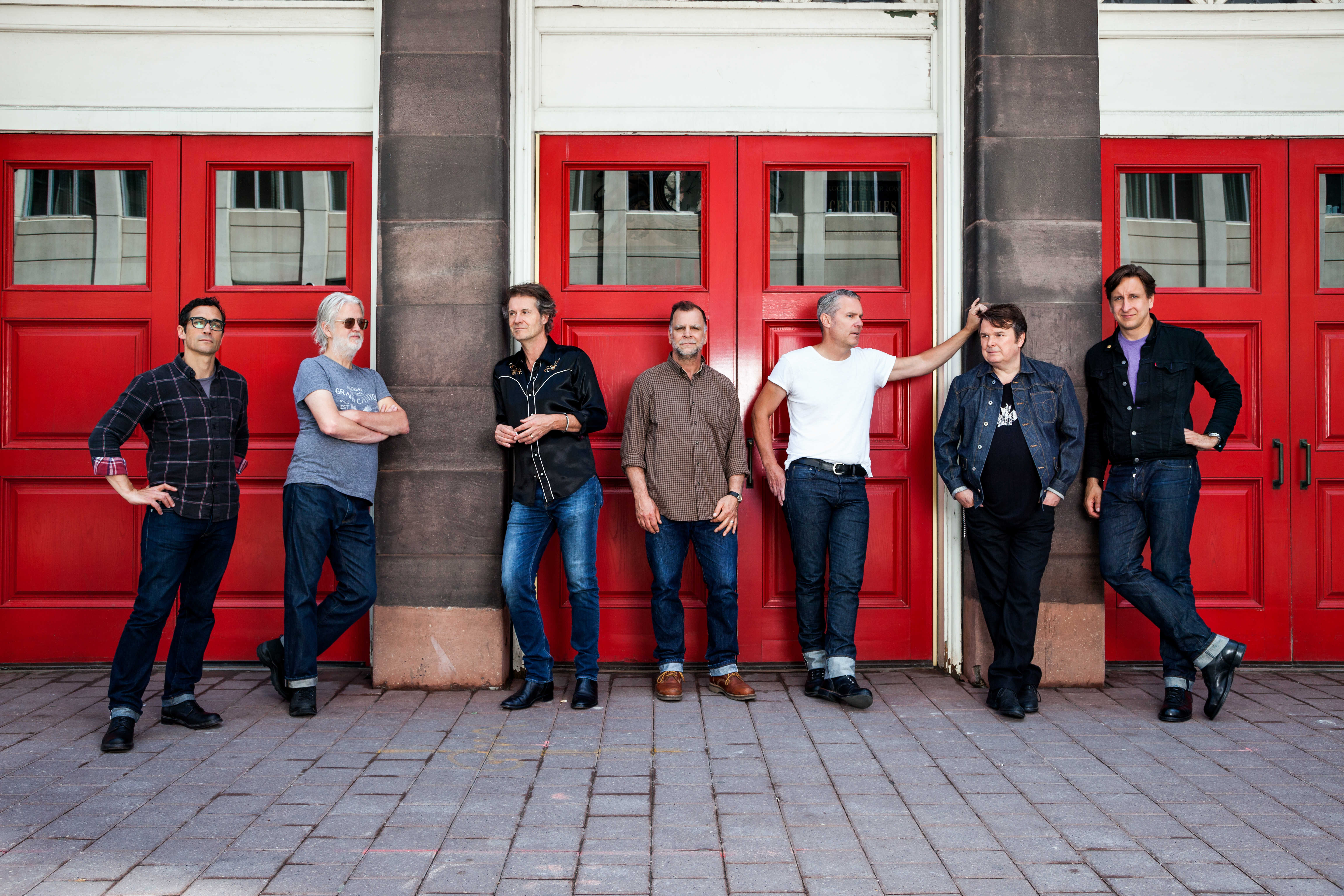 Seven men stand facing either the camera or one another. They all wear jeans and either a t-shirt or a button down shirt. In front of three sets of red doors that lead from the music hall to the street. Two brown stone columns divide the sets of doors. Above the doors are white panelling.