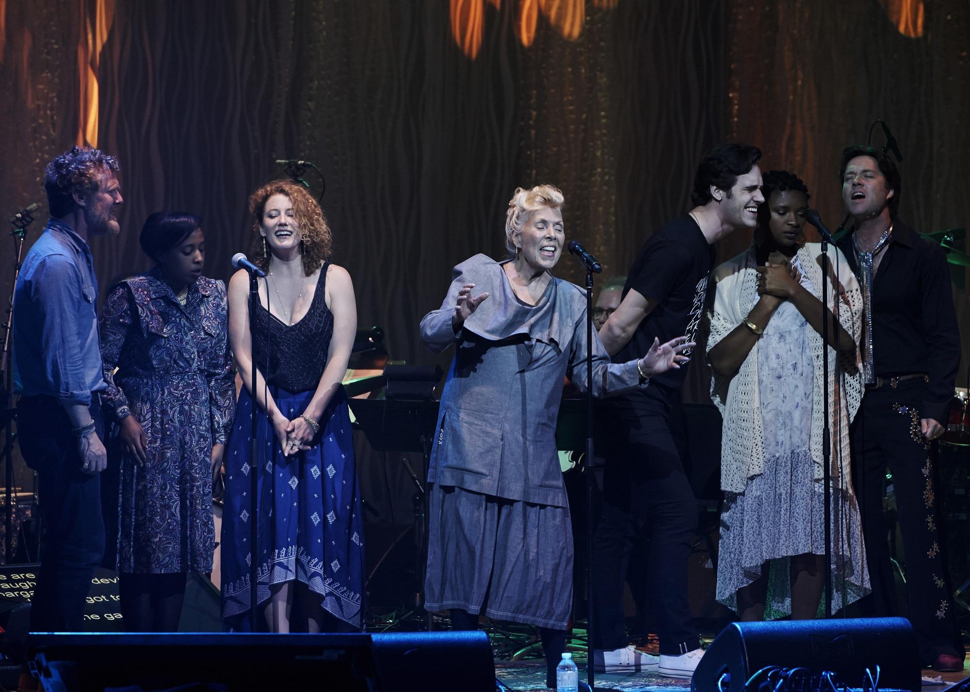Sept interprètes sur scène, dont JoniMitchell au centre chantant les yeux fermés, vêtue d'une robe mauve pâle. Deux groupes de trois interprètes partagent un microphone sur pied de chaque côté d'elle.