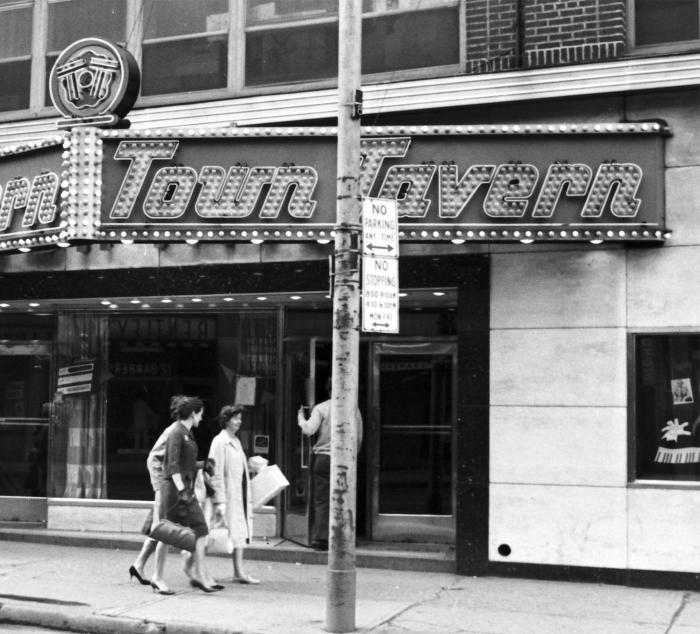 Deux personnes marchent sur un trottoir devant une façade de bâtiment urbain. Au centre, il y a une entrée avec un panneau indiquant «Town Tavern».