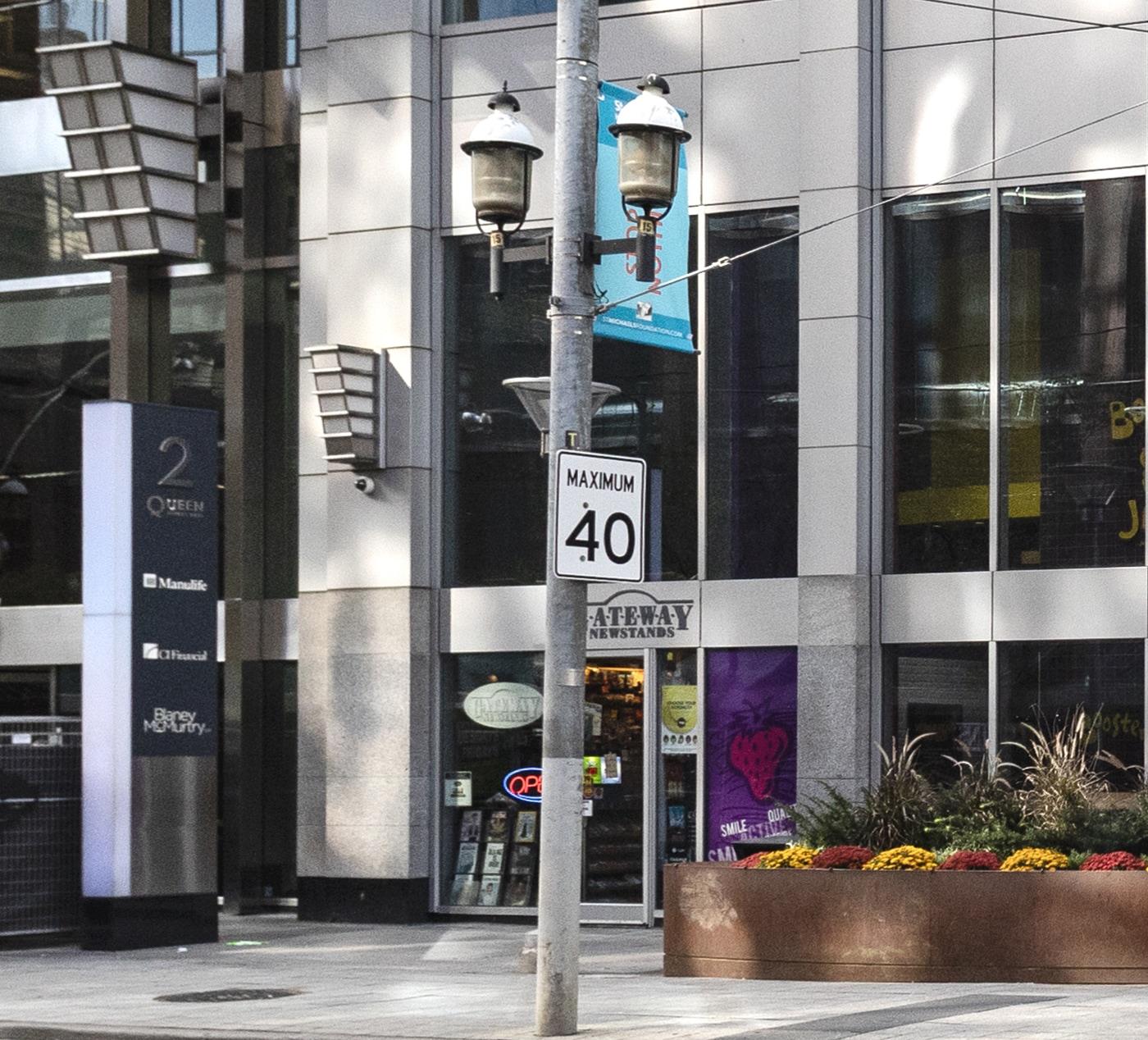 La photo montre un immeuble contemporain gris accueillant un magasin de journaux ainsi que le trottoir devant la façade. On retrouve des plantes aux couleurs d'automne à la droite du magasin. En premier plan, il y a un lampadaire avec un panneau indiquant «Maximum40».