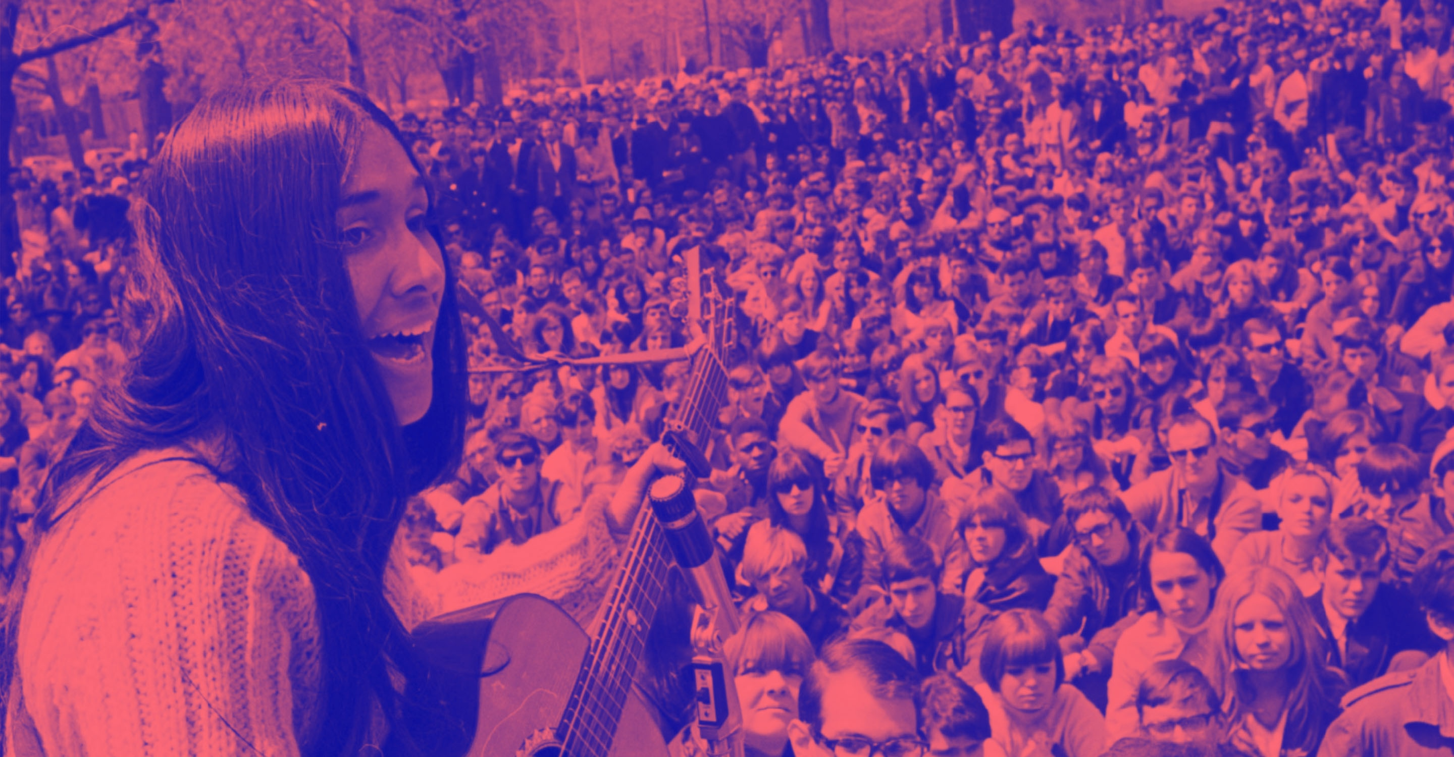 A woman with long hair playing acoustic guitar to a large outdoor crowd.