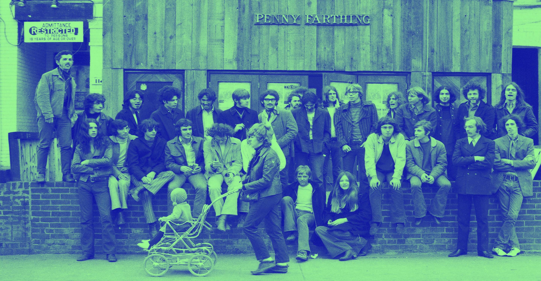 Un groupe de personnes debout contre un bâtiment, posant pour une photo
