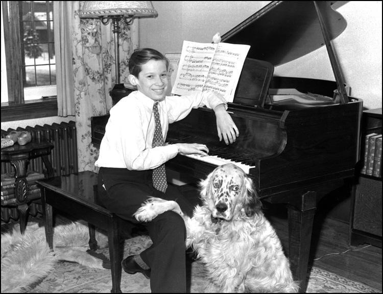 The child Glenn Gould is pictured alongside his dog Nicky. Gould is sitting on a chair next to his piano. He is dressed in a smart attire wearing a white dress shirt and a tie. Gould is sitting in a casual pose with his left arm resting on top of the piano and his right hand touching the keyboard. His white and black furred dog places its right fore paw on Gould's right leg. A music sheet is left open on top of his piano.