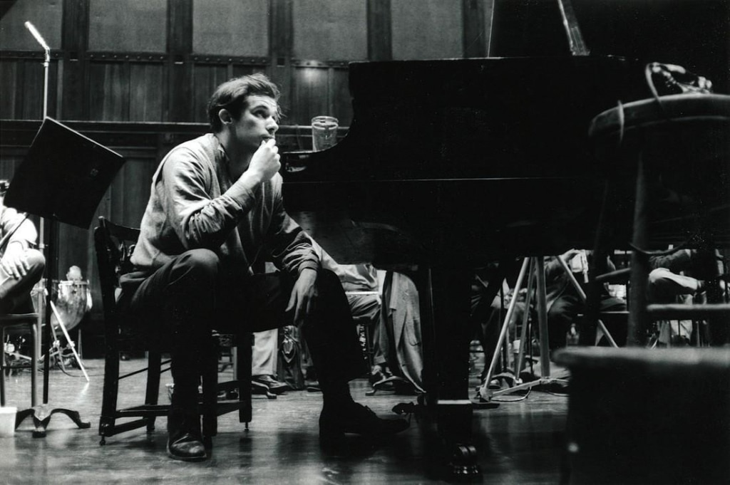 A man dressed in a light coloured shirt and dark pants sits on a small chair next to a piano in a concert hall. Glenn Gould is touching his chin and is in a contemplative state. Members of an orchestra are visible in the background.