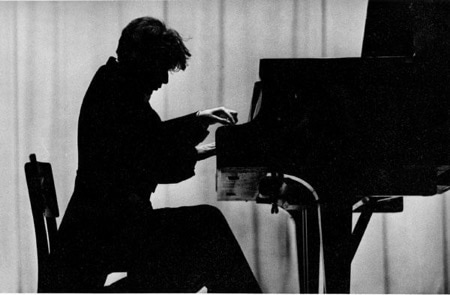 Glenn Gould dressed in a long tailed tuxedo plays on the piano in the Soviet Union in 1957. Gould appears on this image as a dark silhouette in front of a light colored curtain. Gould is deeply invested in his performance. His left leg is pulled under his chair and his hair falls forward under the intensity of his performance.