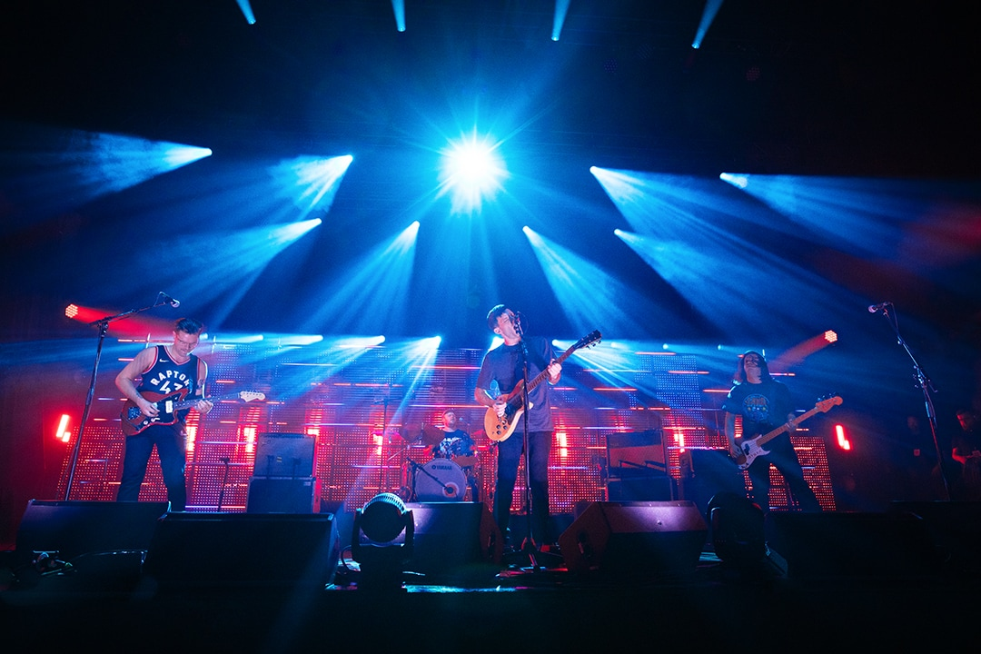 Lit by blue and red stage lights PUP members perform their song Morbid Stuff at the Carlu in Toronto during the 2019 Polaris Music Prize Gala. Nestor Chumak; Steve Sladkowski and Stefan Babcock play on different types of guitars while Zack Mykula performs on drums.
