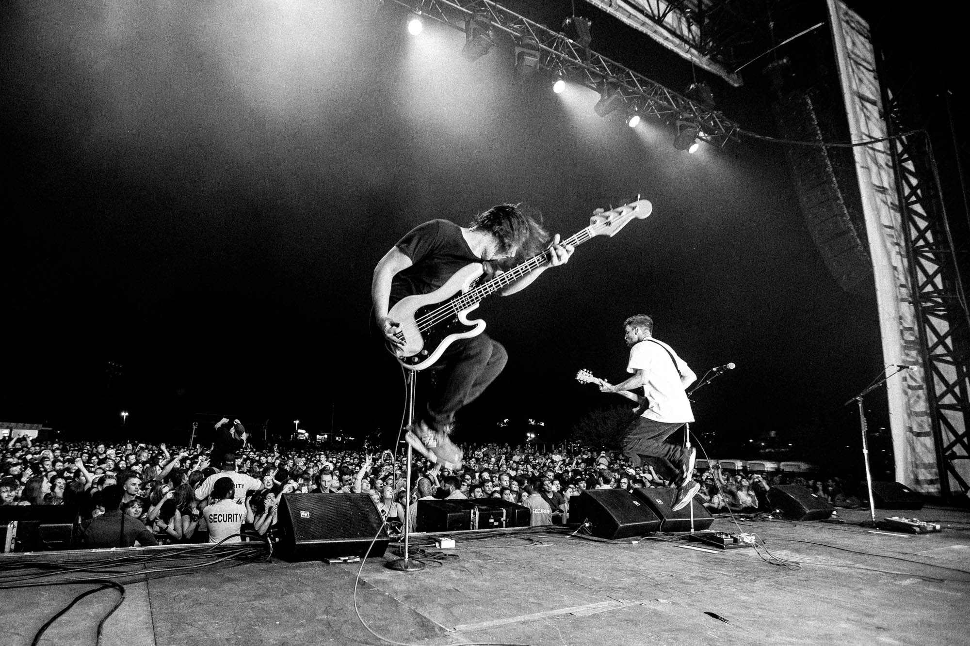 Two men are on stage in front of a large crowd. They are both caught by the camera mid-jump while holding their guitars.