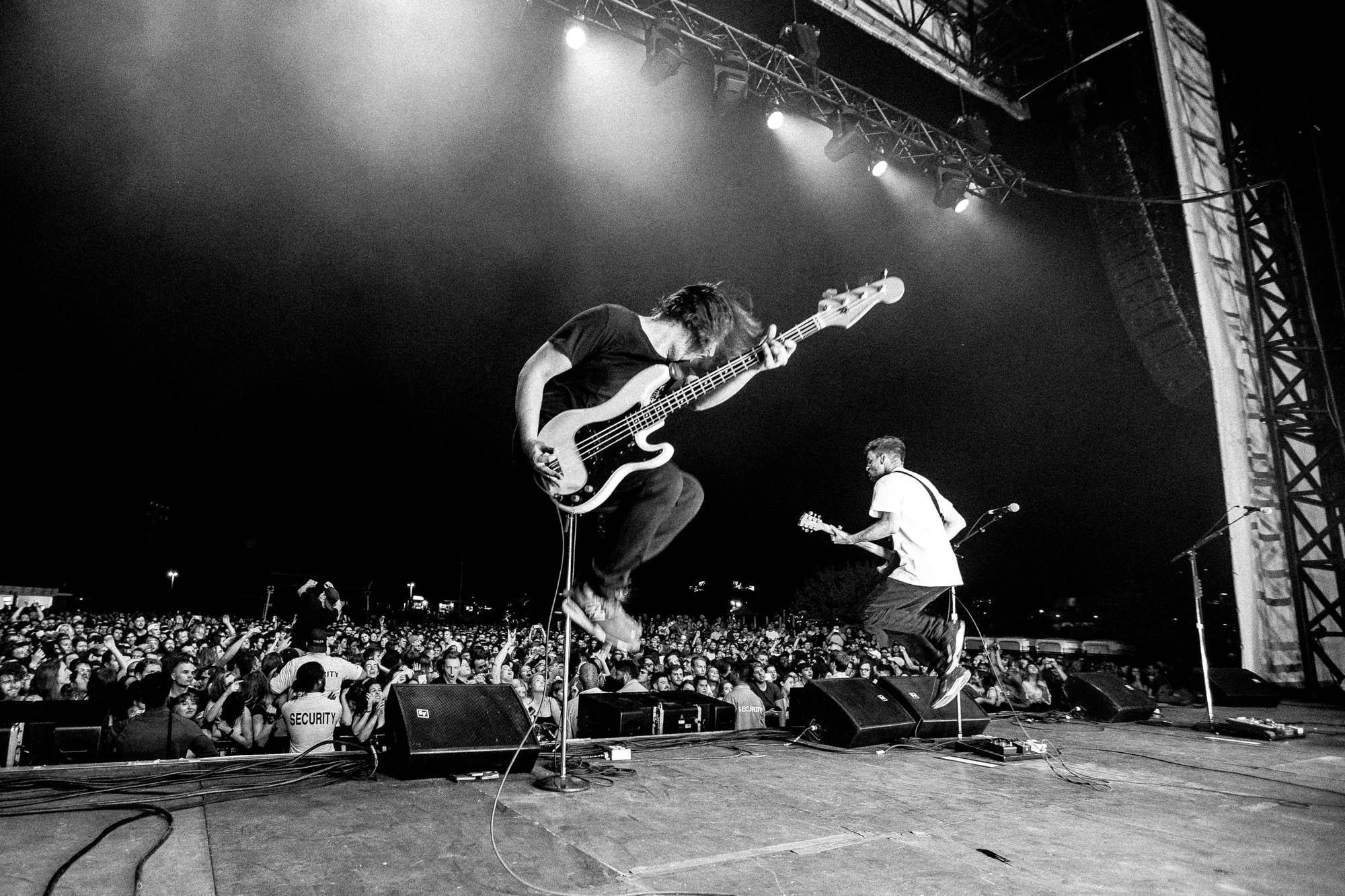 Deux hommes sont sur scène devant une foule nombreuse. Ils sont tous les deux capturés par l'appareil photo en train de sauter tout en tenant leurs guitares.