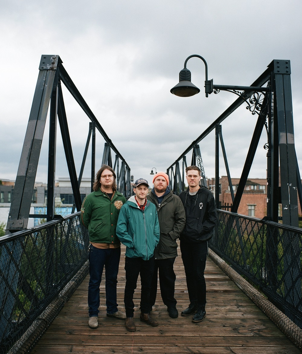 Members of the punk band PUP (Nestor Chumak; Steve Sladkowski; Zack Mykula; Stefan Babcock) pose for a picture on a pedestrian bridge on a cloudy day in Toronto. They are dressed casually in jeans and light coats. They are keeping their hands in the pockets of their coats. The rooftops of small residential buildings are visible in the background.
