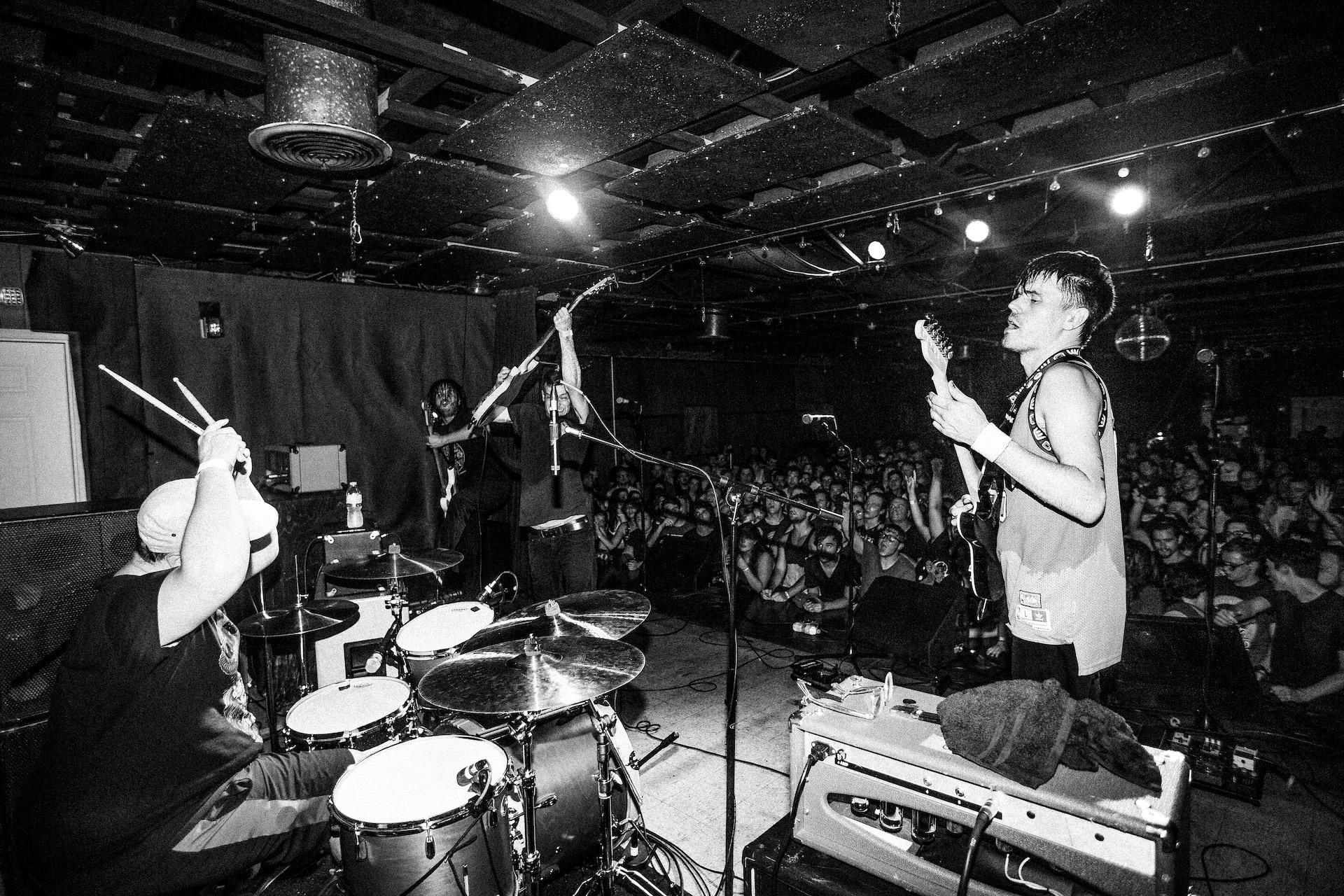 Une image en noir et blanc d'un groupe sur scène devant un large public. Le batteur est sur le point de frapper la batterie tandis qu'un homme tenant une guitare basse le regarde.