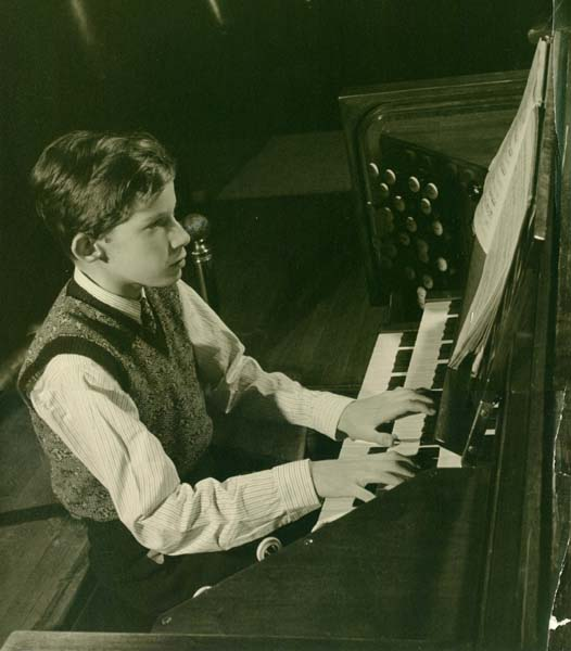 In a faded black and white photo, a young boy sits at an organ in the concert hall of the Toronto Conservatory of Music around the year 1945.